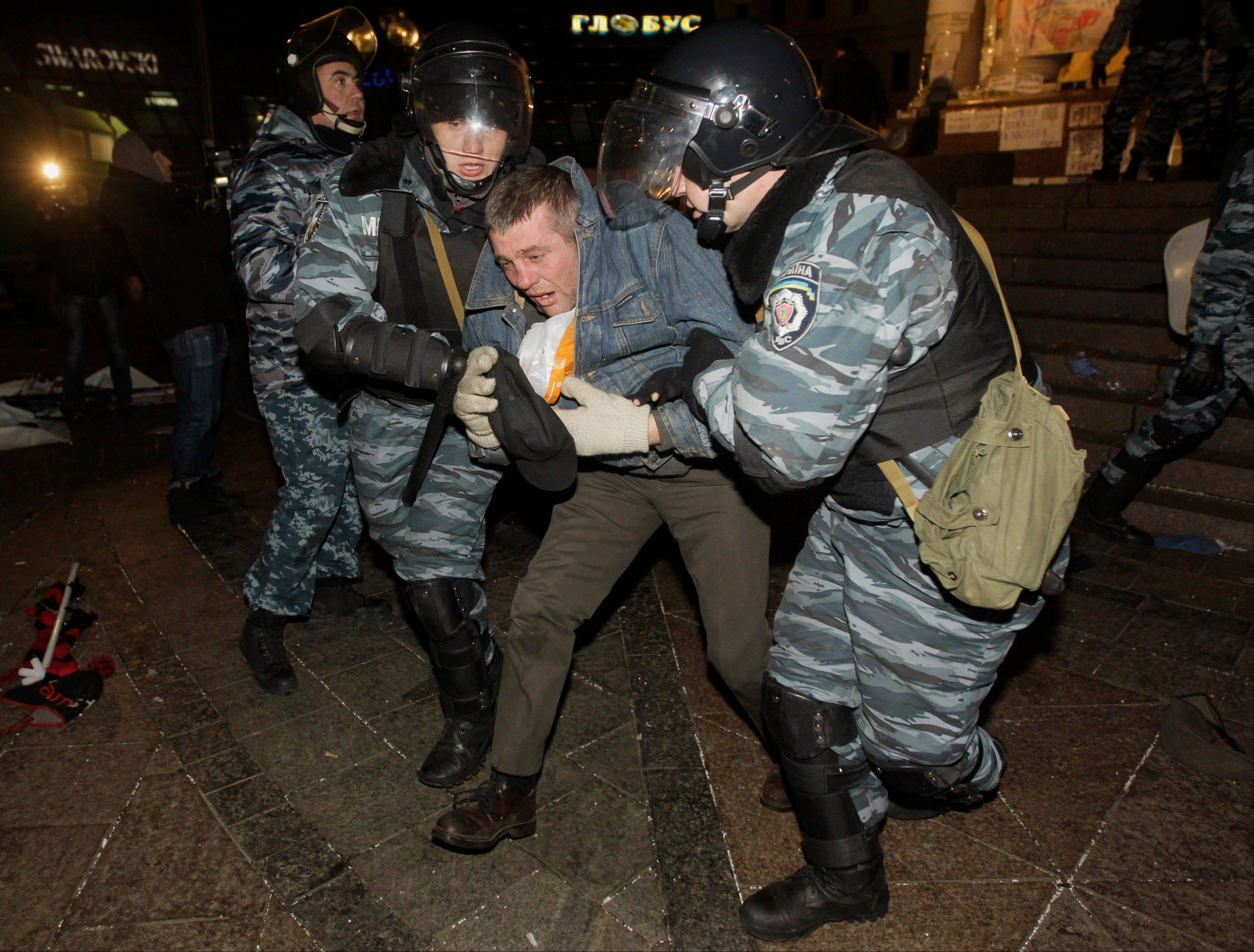 Ukrainian riot police officers detain an activist Saturday during a rally demanding the resignation of President Viktor Yanukovych, at the Independence Square in downtown Kiev, Ukraine.