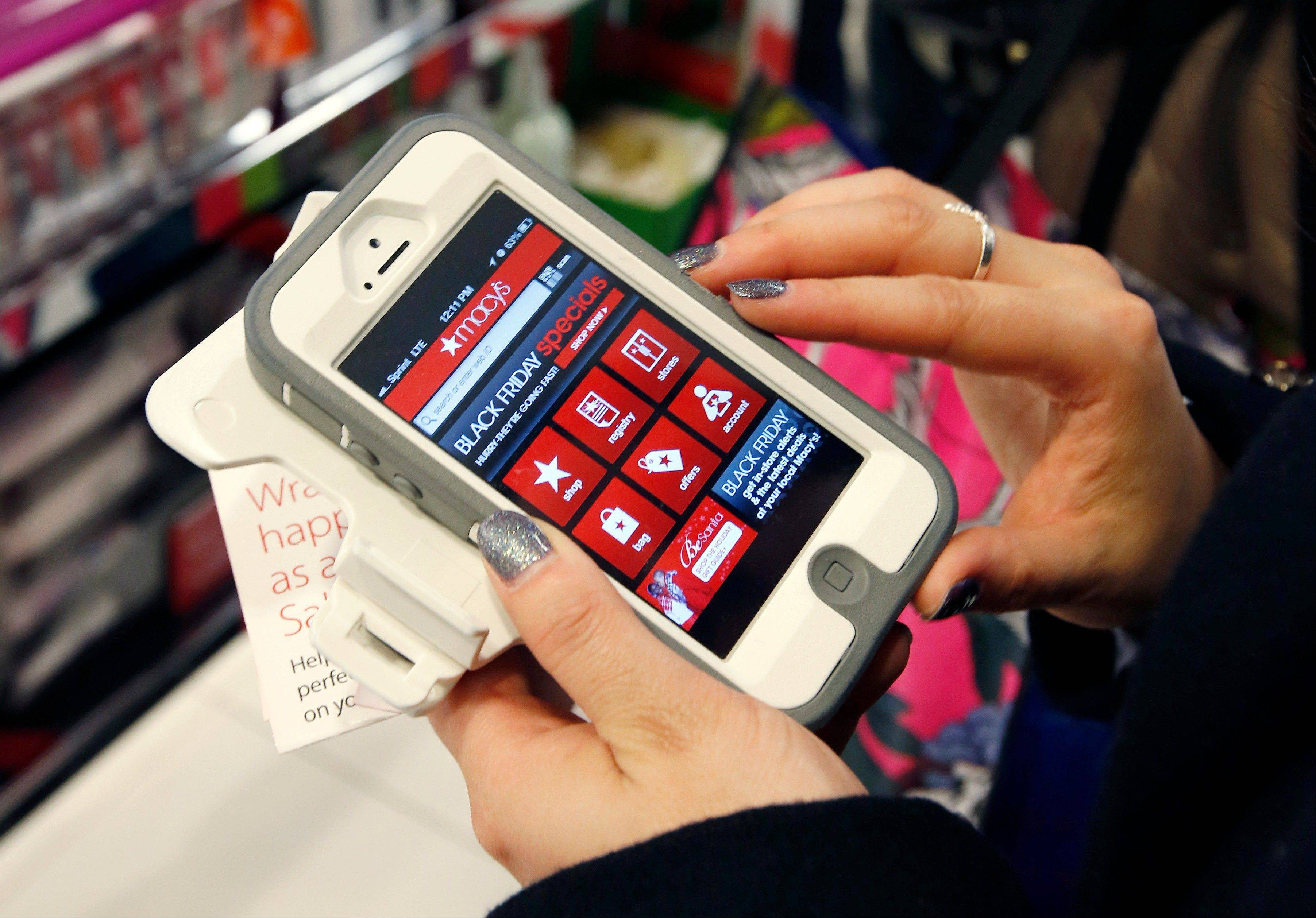 Tashalee Rodriguez of Boston uses a smartphone app while shopping at Macy's in downtown Boston. Big retailers are offering apps that feature a hefty selection of deals.