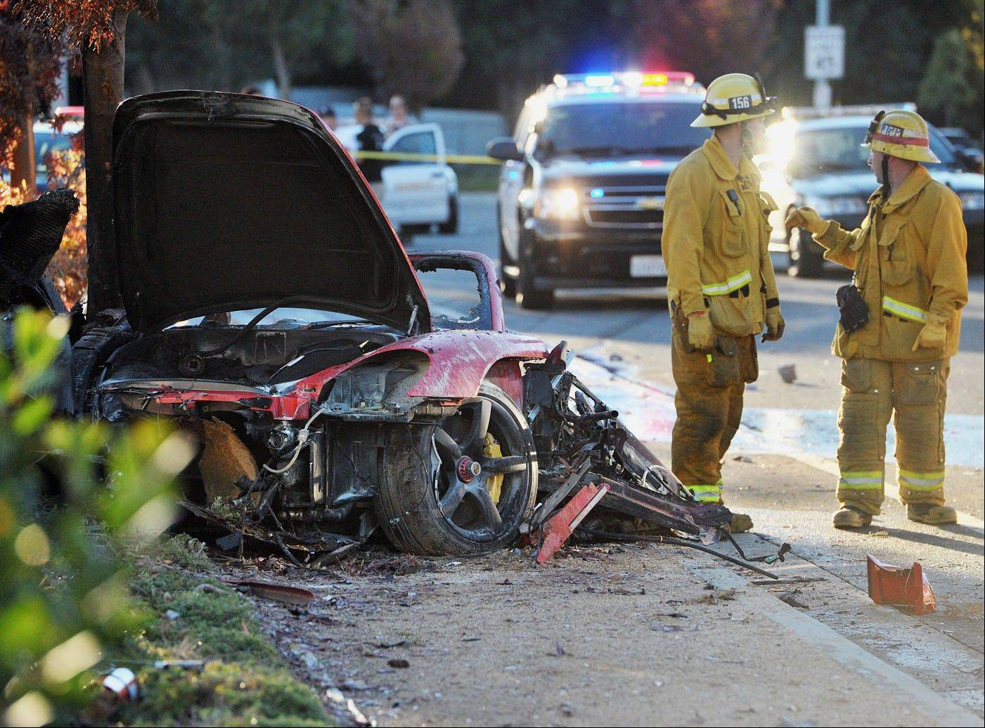 "First responders gather evidence near the wreckage of a Porsche sports car that crashed into a light pole on Hercules Street near Kelly Johnson Parkway in Valencia on Saturday. A publicist for actor Paul Walker says the star of the ""Fast & Furious"" movie series has died in a car crash north of Los Angeles. He was 40."