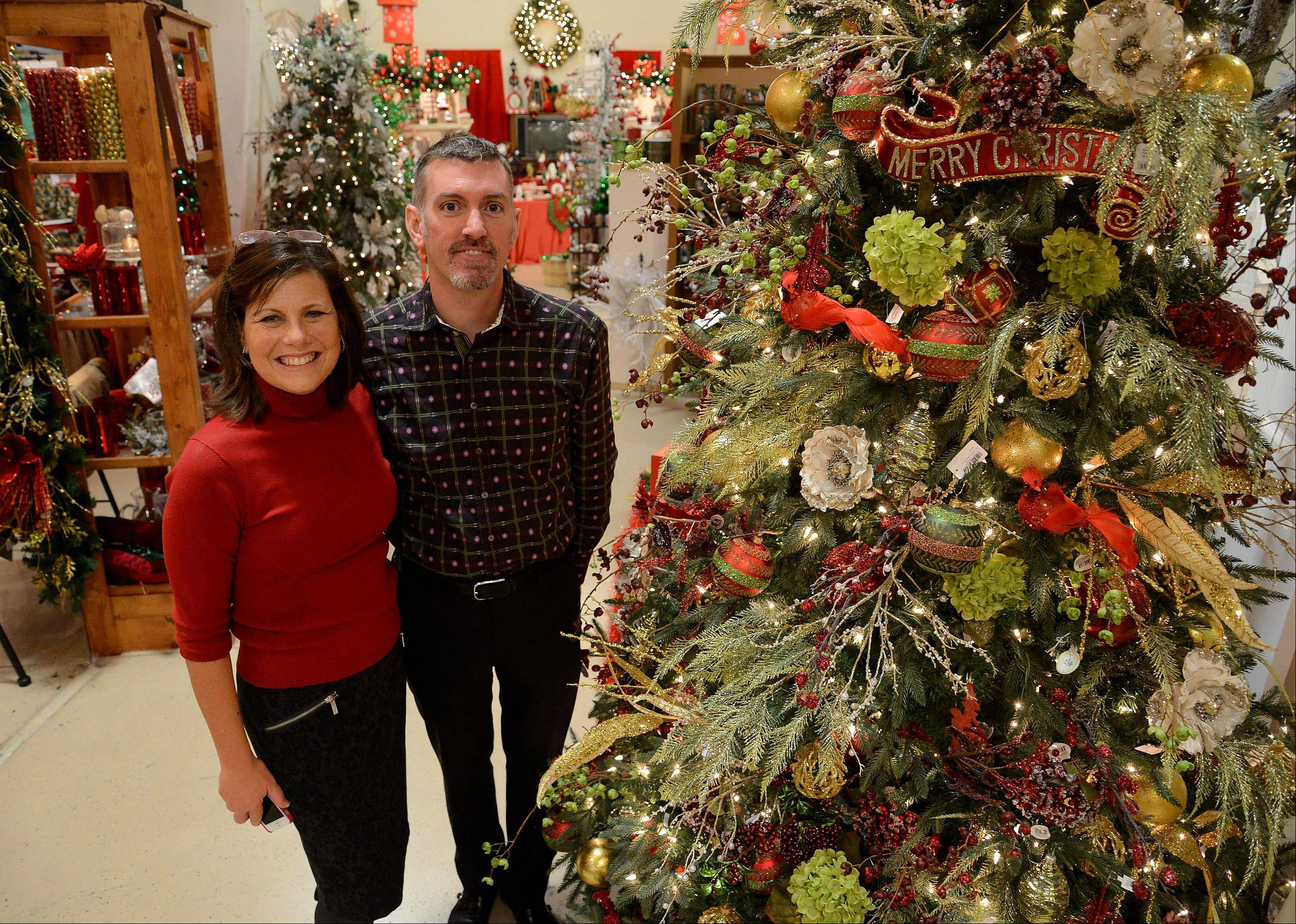 Owner Laurie Kane and designer James Whitehead of Treetime Christmas Creations in Lake Barrington, standing next to a tree with updated traditional colors and feel.