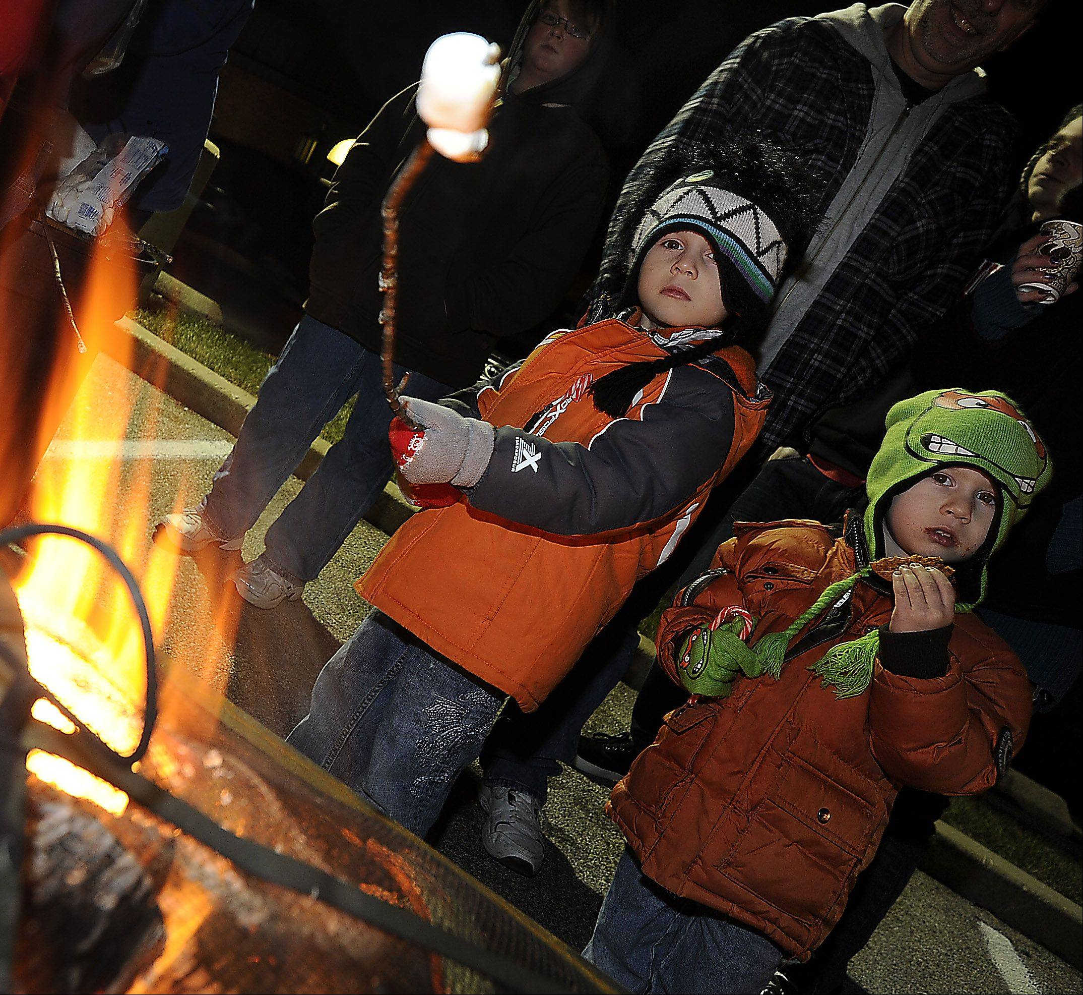 Frank Katz, 5, and his brother, Tommie, 3, of Prospect Heights roast marshmallows before visiting with Santa at the Prospect Heights tree-lighting held at city hall on Saturday.