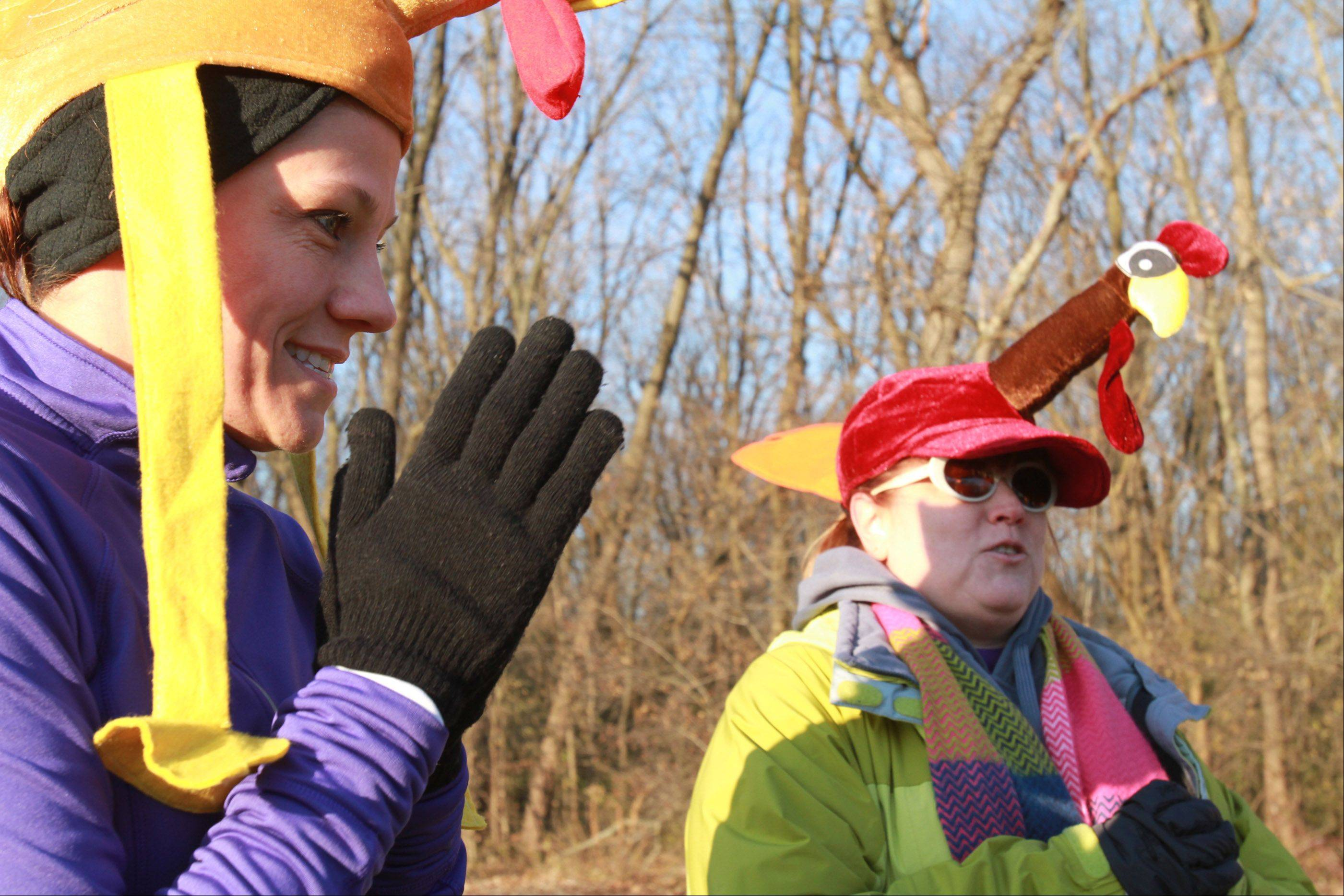 Shelly Lamb of Roselle and Tania Sorrentino of Wheeling try to say warm before the start of the Schaumburg Half Marathon and 5K Turkey Trot on Saturday which runs through Busse Woods Forest Preserve near Schaumburg.
