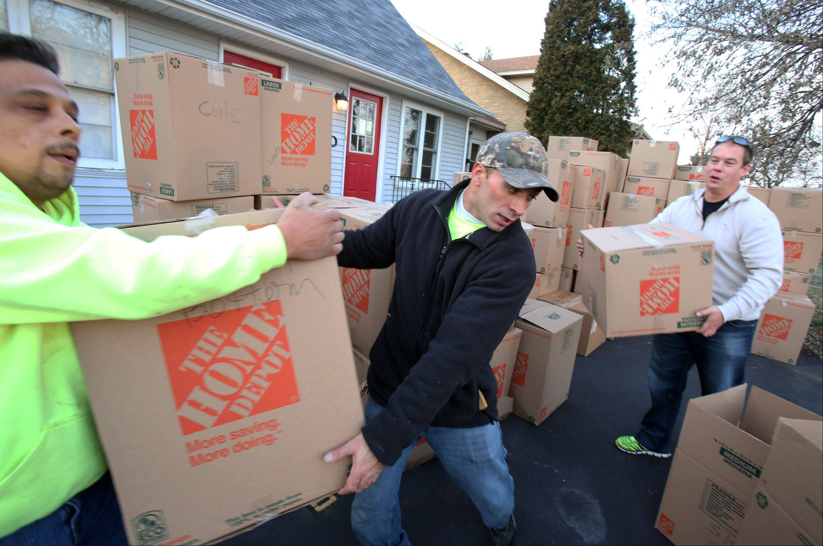 Eddie Guevara takes a box from John Castiglione, both crew leaders at North Village Group, as the companies CEO Sean Sandona bring up a another box as workers from the Des Plaines-based construction supply firm load boxes filled with winter clothing, construction safety equipment, and general items into a truck on Friday in Des Plaines which are destined for tornado-ravaged Washington on Saturday.
