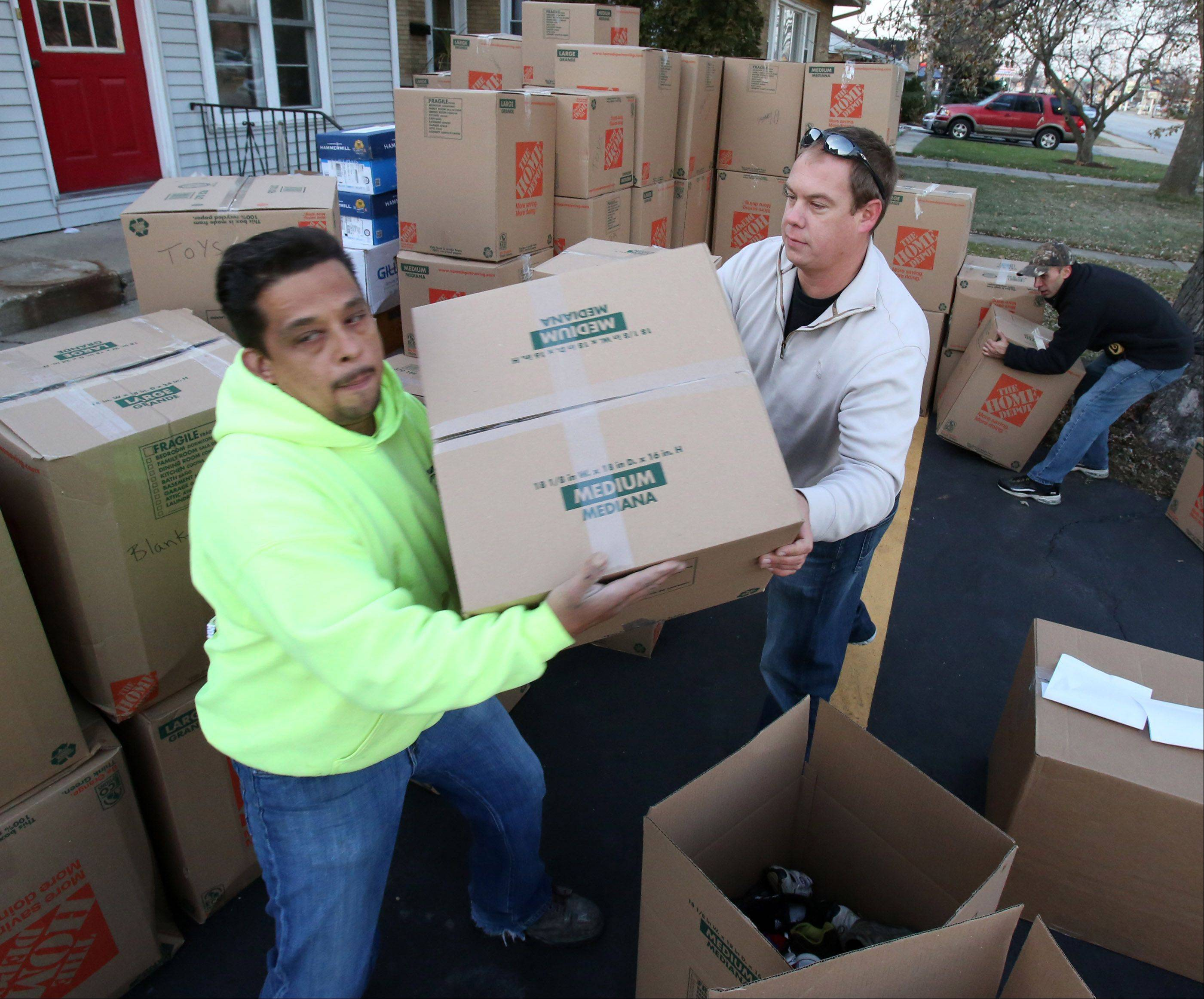 Eddie Guevara takes a box from North Village Group CEO Sean Sandona as workers from the Des Plaines-based construction supply firm load boxes filled with winter clothing, construction safety equipment, and general items into a truck on Friday in Des Plaines which are destined for tornado-ravaged Washington on Saturday.