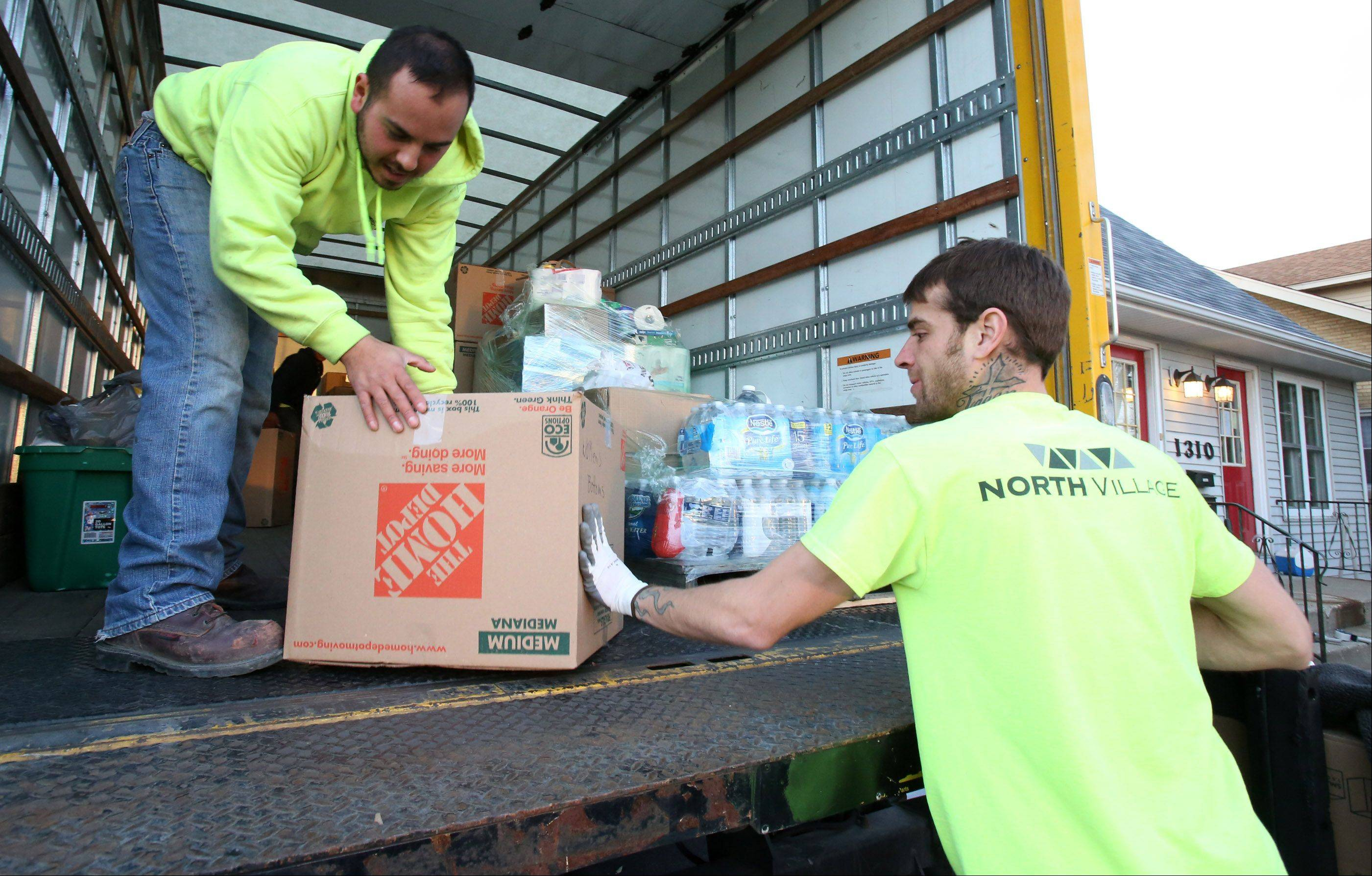 Matt Nelson, project manager at North Village Group slides a box filled with winter clothing to Jose Cabral in a truck on Friday at the Des Plaines-based construction supply firm, destined for tornado-ravaged Washington on Saturday.
