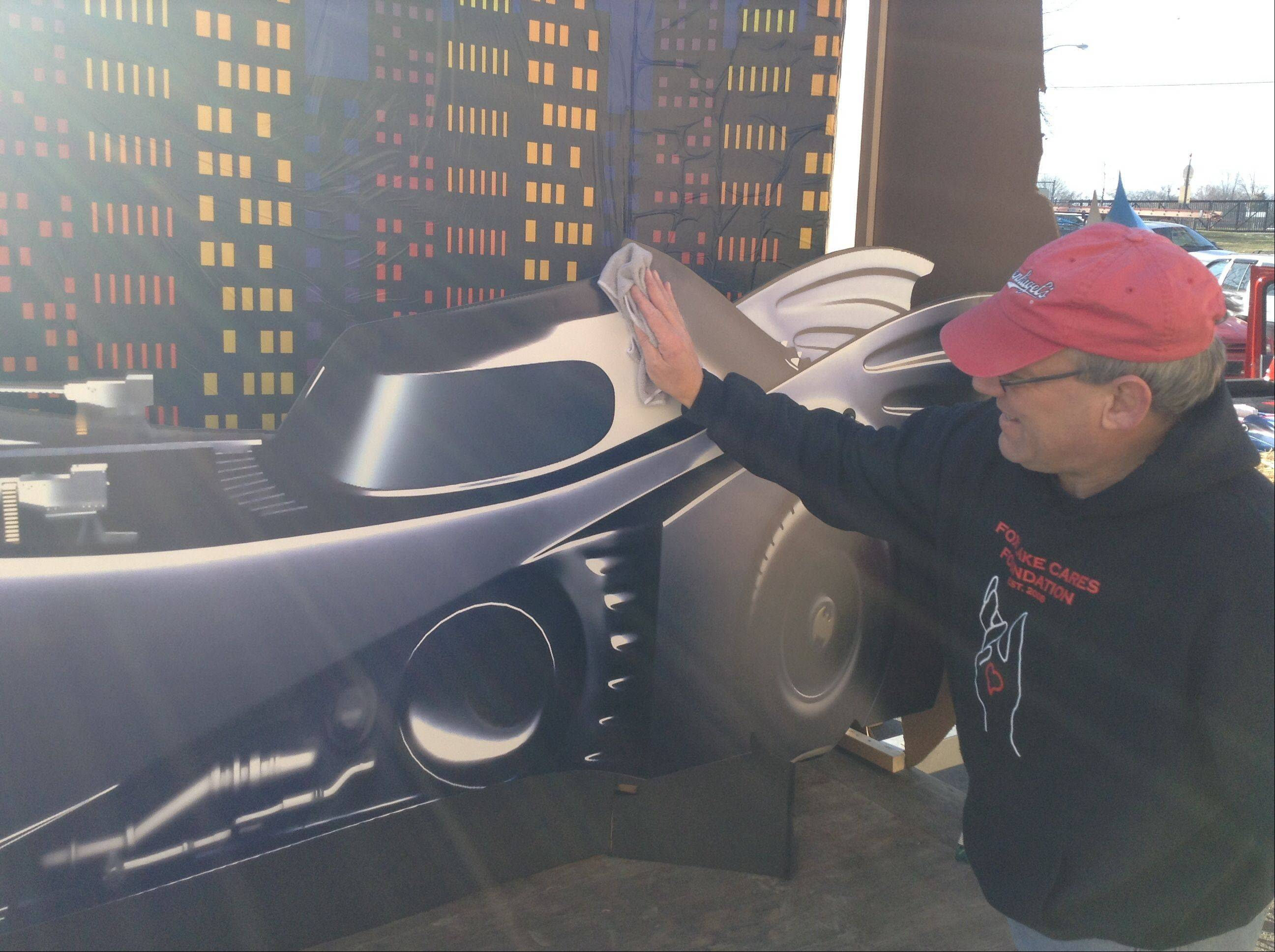 David Gauger waxes the Batmobile on the Fox Lake Cares float before the parade begins.
