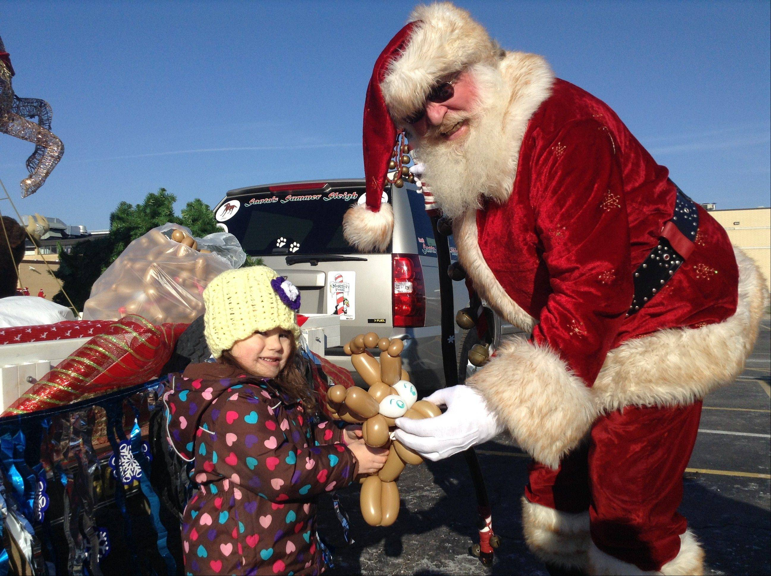 Russell Lissau/rlissau@dailyherald.comNevaeh Hooper, 3, gets a balloon reindeer from Santa before the parade begins.