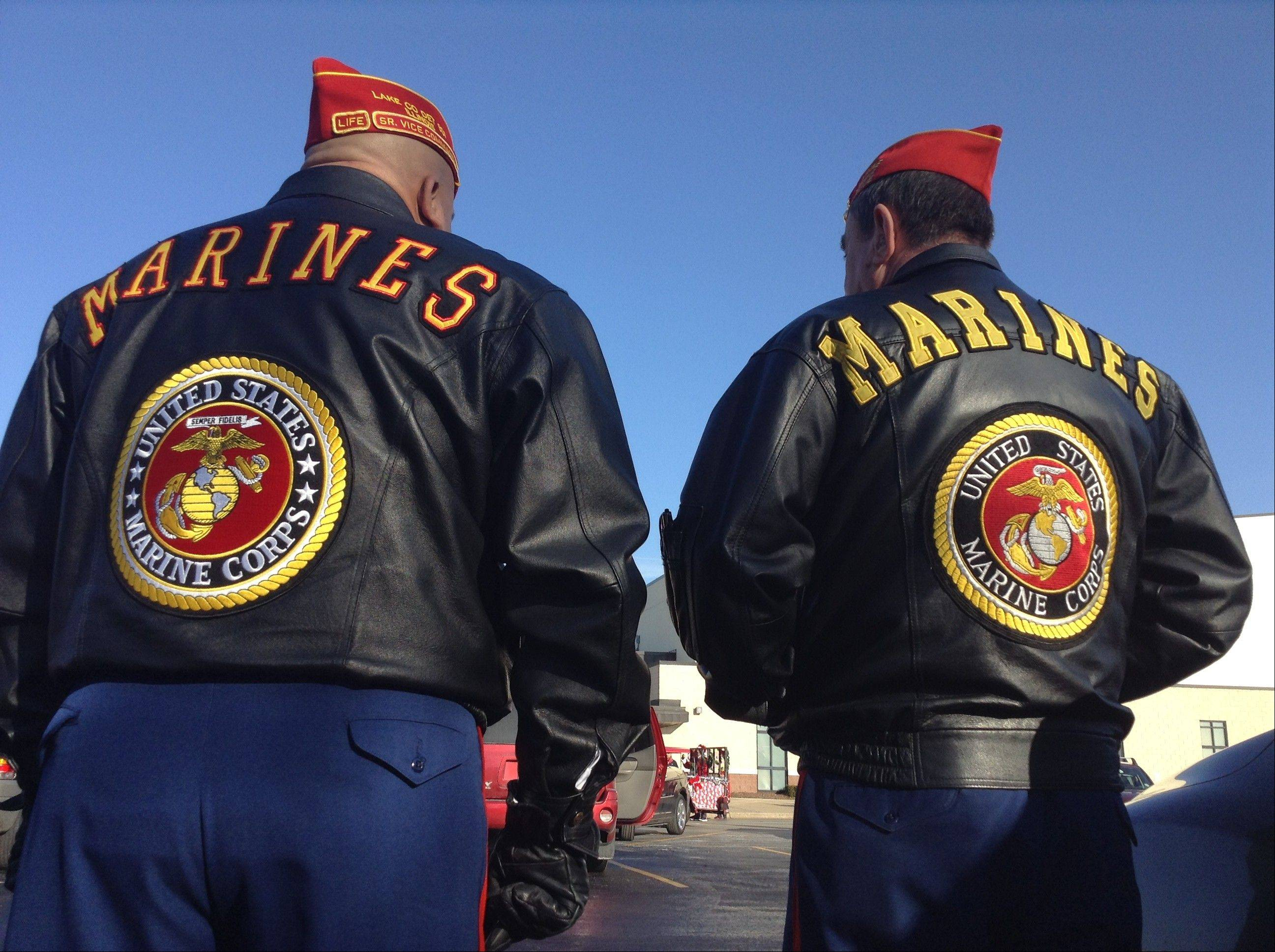 Russell Lissau/rlissau@dailyherald.com Retired Marines Roy Cuevos, left, and Toy Keeton wait to march in the parade as part of the color guard.