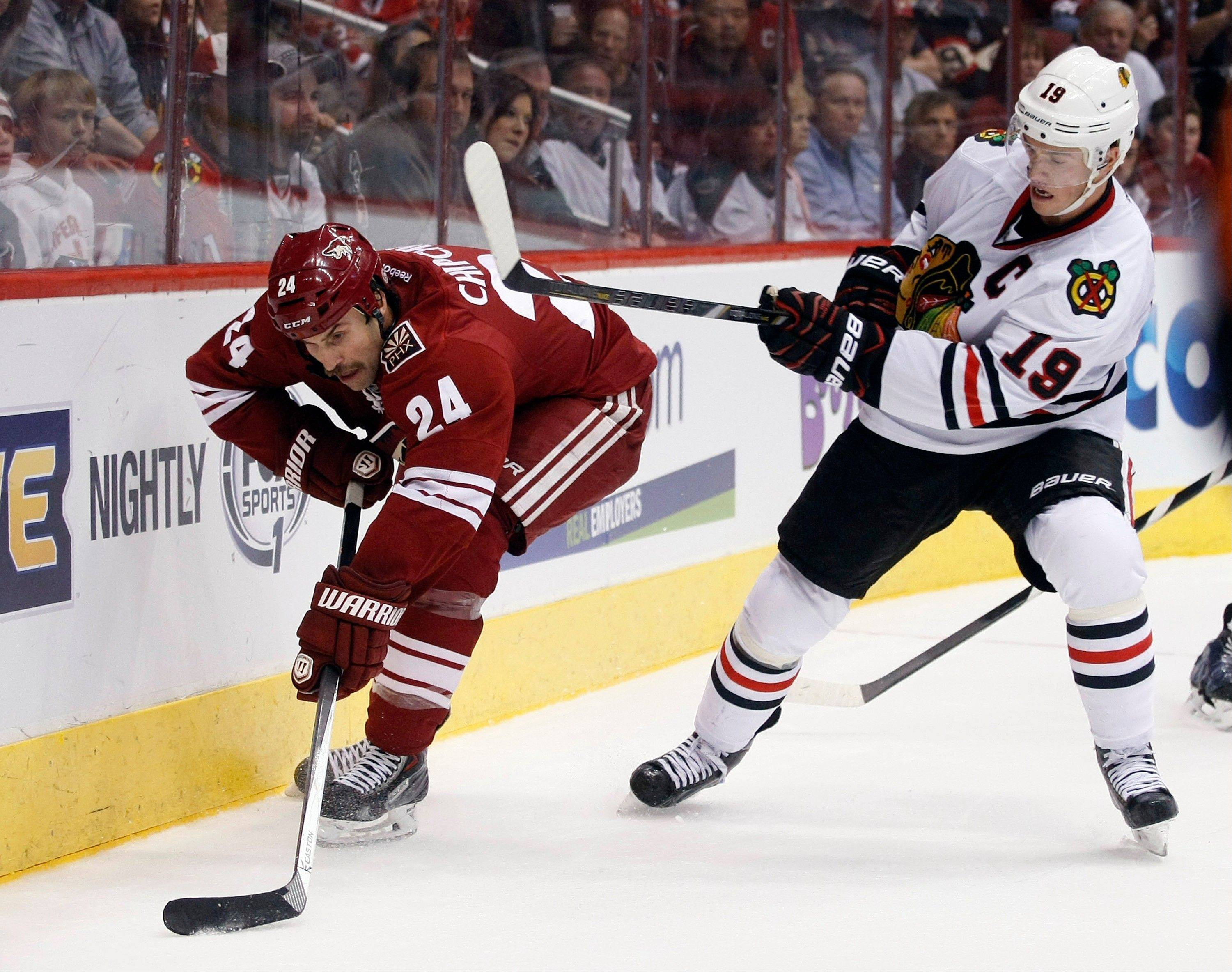 The Blackhawks' Jonathan Toews battles the Coyotes' Kyle Chipchura for the puck in the second period Saturday night.