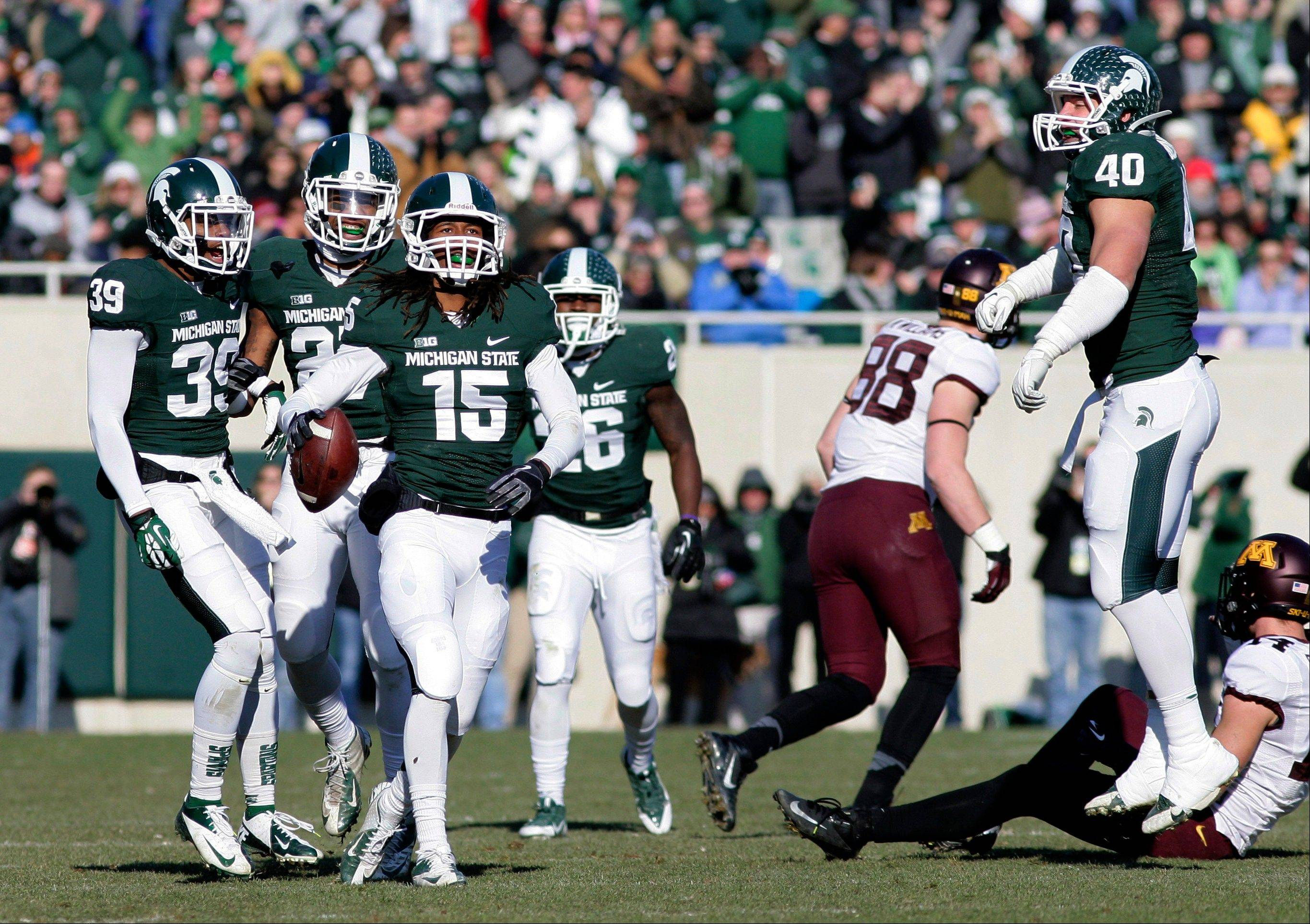 Michigan State players, including Jermaine Edmondson (39), Kurtis Drummond, Trae Waynes (15), R.J. Williamson (26) and Max Bullough (40), celebrate Waynes' interception against Minnesota during the second quarter of an NCAA college football game, Saturday, Nov. 30, 2013, in East Lansing, Mich.