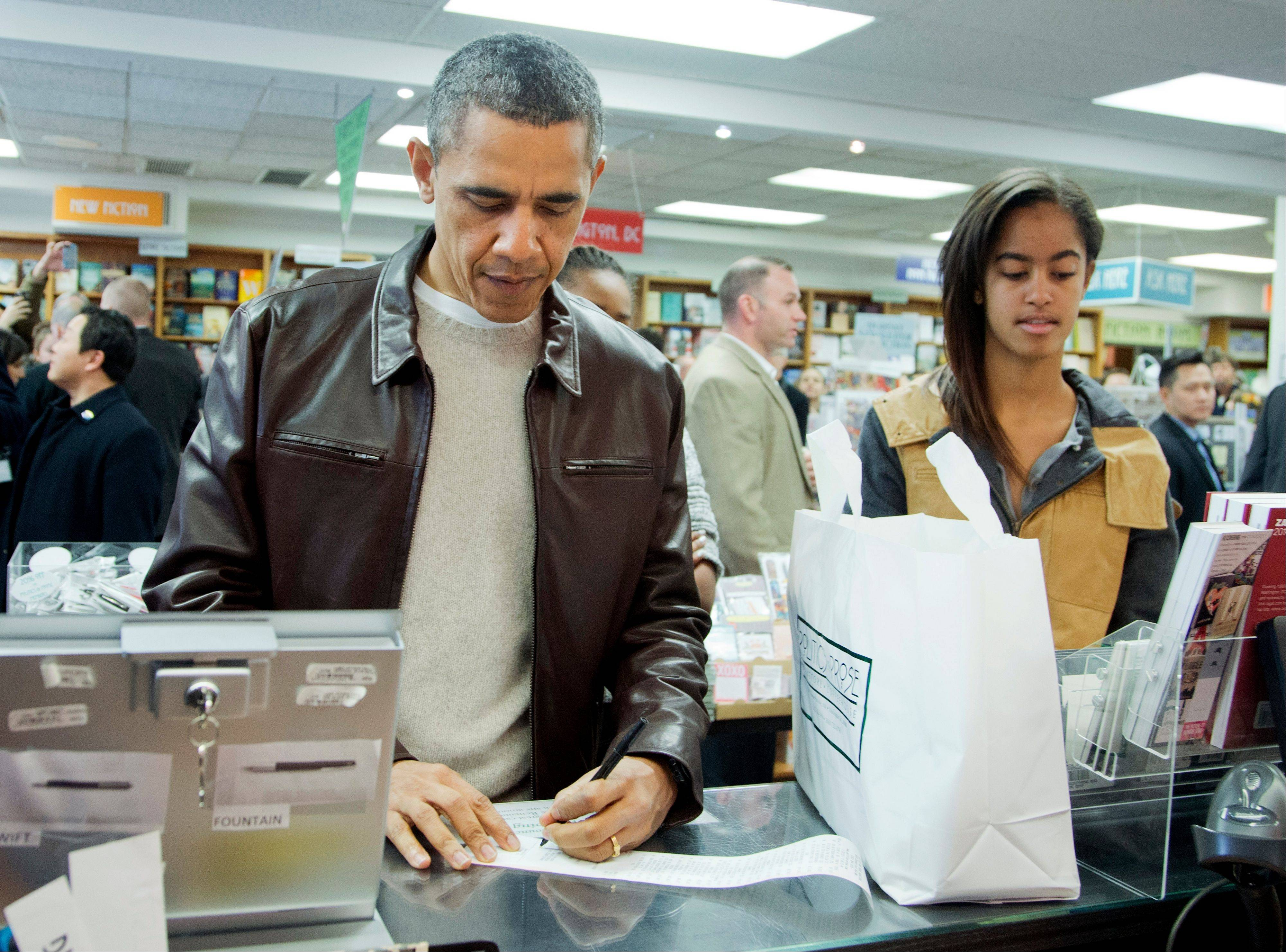 President Barack Obama, with daughters Sasha, center partially hidden, and Malia, pays for his purchase Saturday at the local bookstore Politics and Prose in Washington.