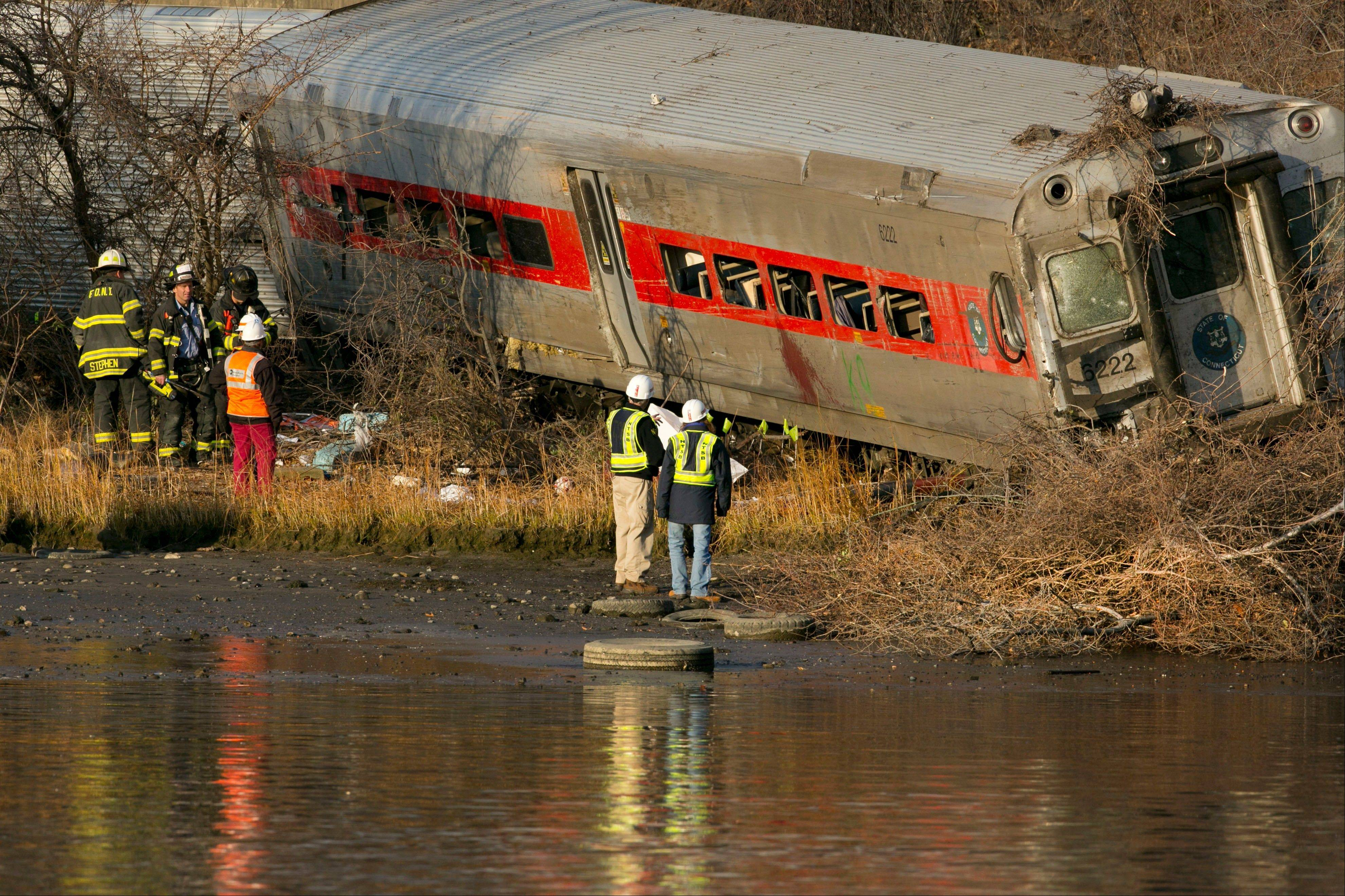 Officials with the National Transportation Safety Board inspect a derailed Metro North commuter train where it almost fell into the Harlem River, Sunday.