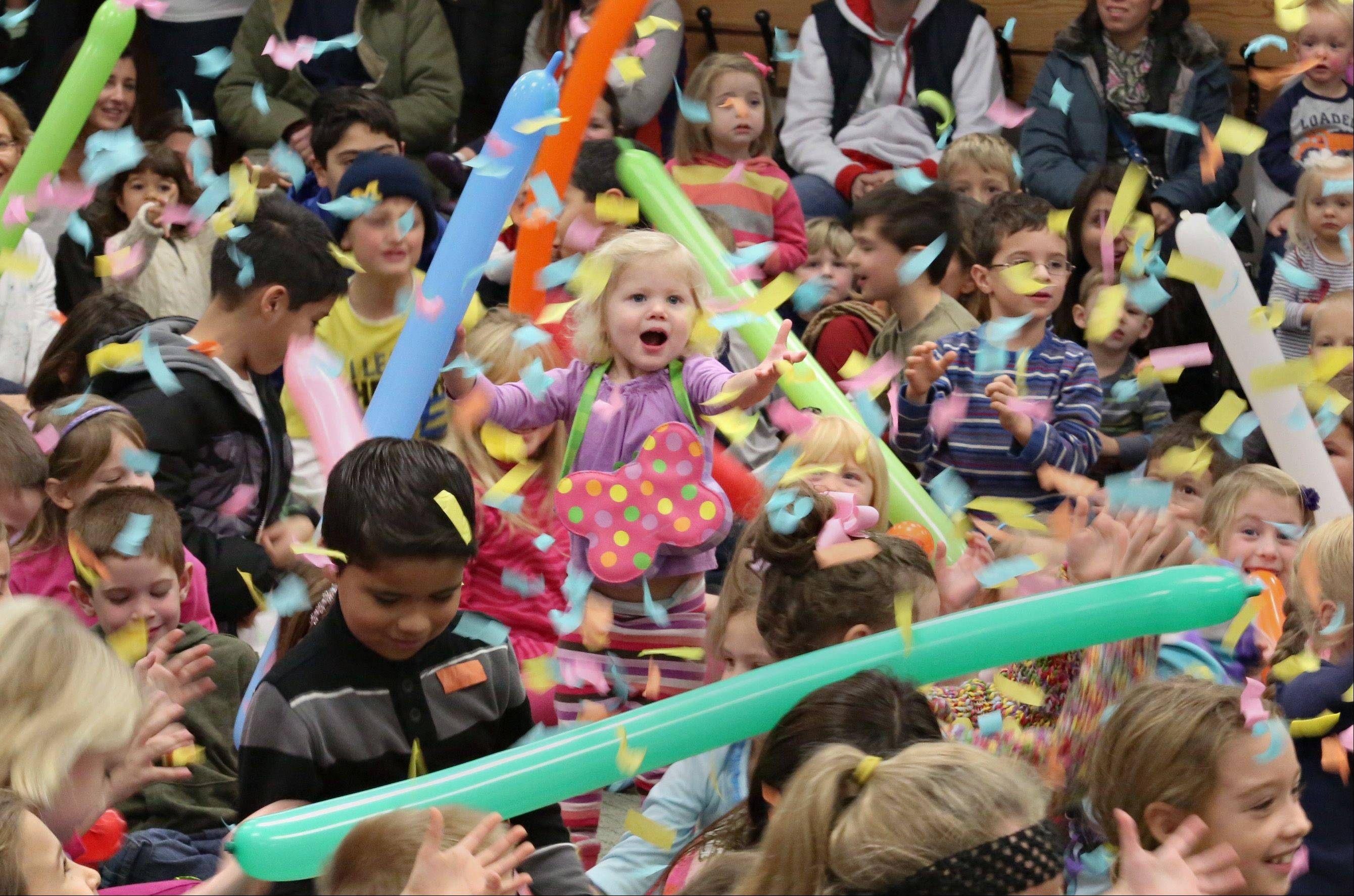 Two-year-old Emilie Patterson, center, of Geneva, is in complete awe of the �balloon barrage� at the end of the Smarty Pants Big Balloon Show Tuesday at the Geneva Public Library.