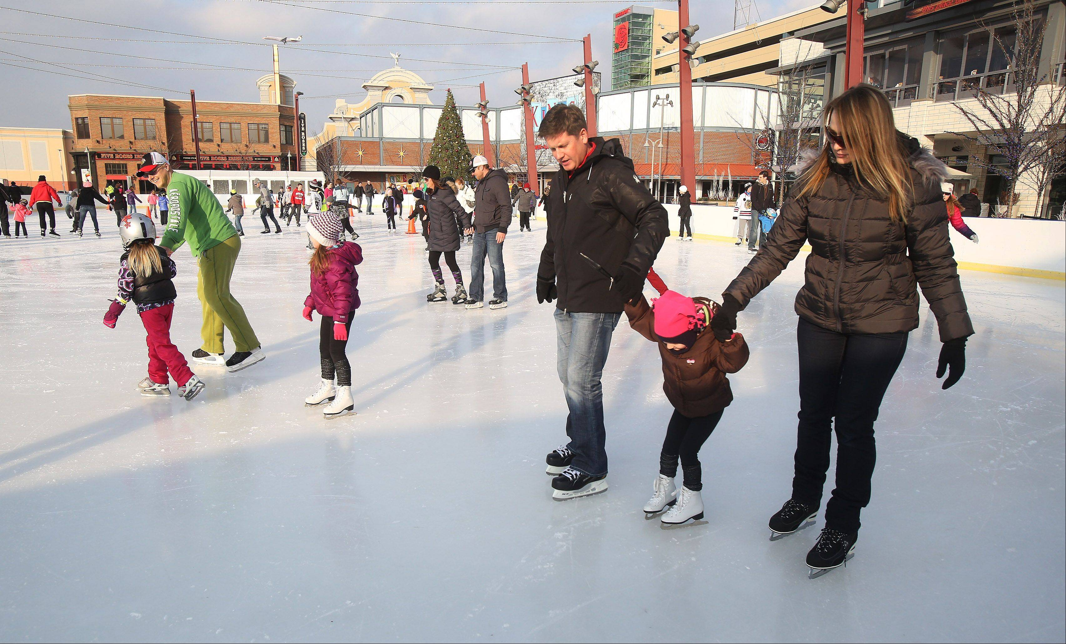 Anna and Darek Fraczek of Northbrook, right, hold onto Izabella, 4, during the free Skating in the Park Sunday at MB Financial Park in Rosemont.
