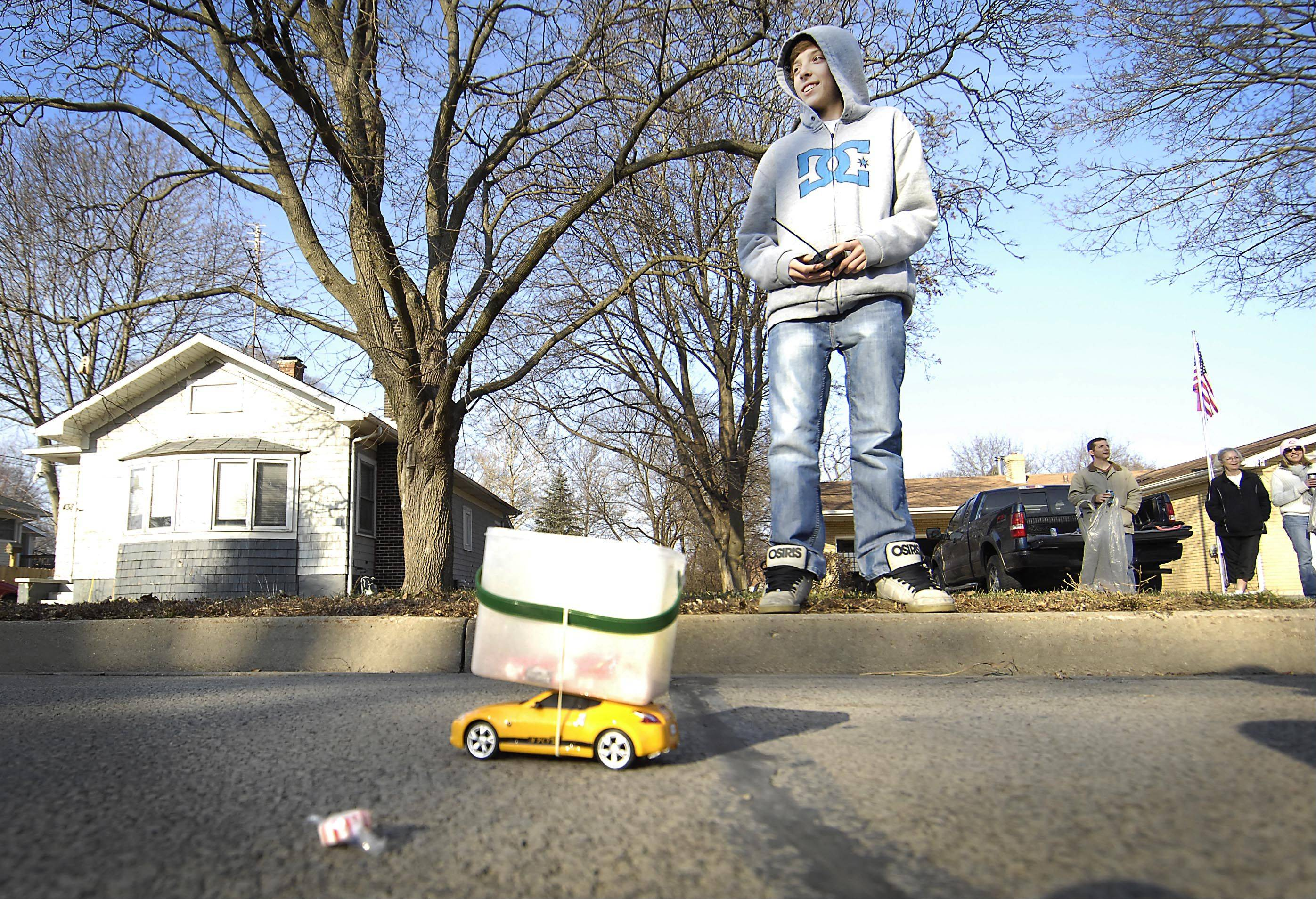 Jacob Franklin, 16, stands on the curb in front of his grandmother�s house Sunday at the Merry Cary Holiday Parade on Main Street in Cary. He used a remote control car with an attached box to collect candy. �It gets a lot of attention,� he said.