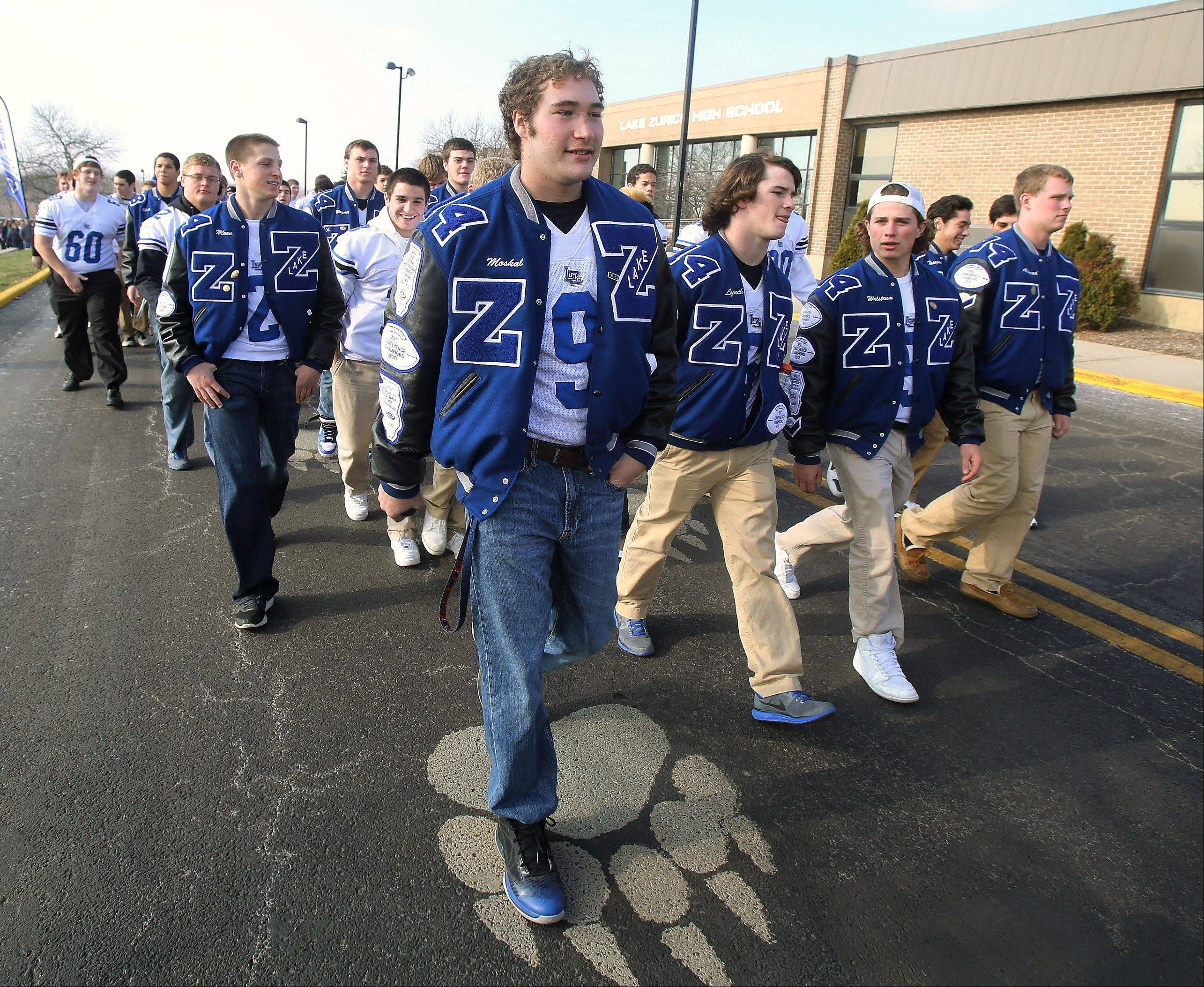 The Lake Zurich High School football team, led by captain Colton Moskal, marches in a parade Sunday after finishing second in the state Class 7A championship this weekend. A rally was held at the school in support of the team and its football season.