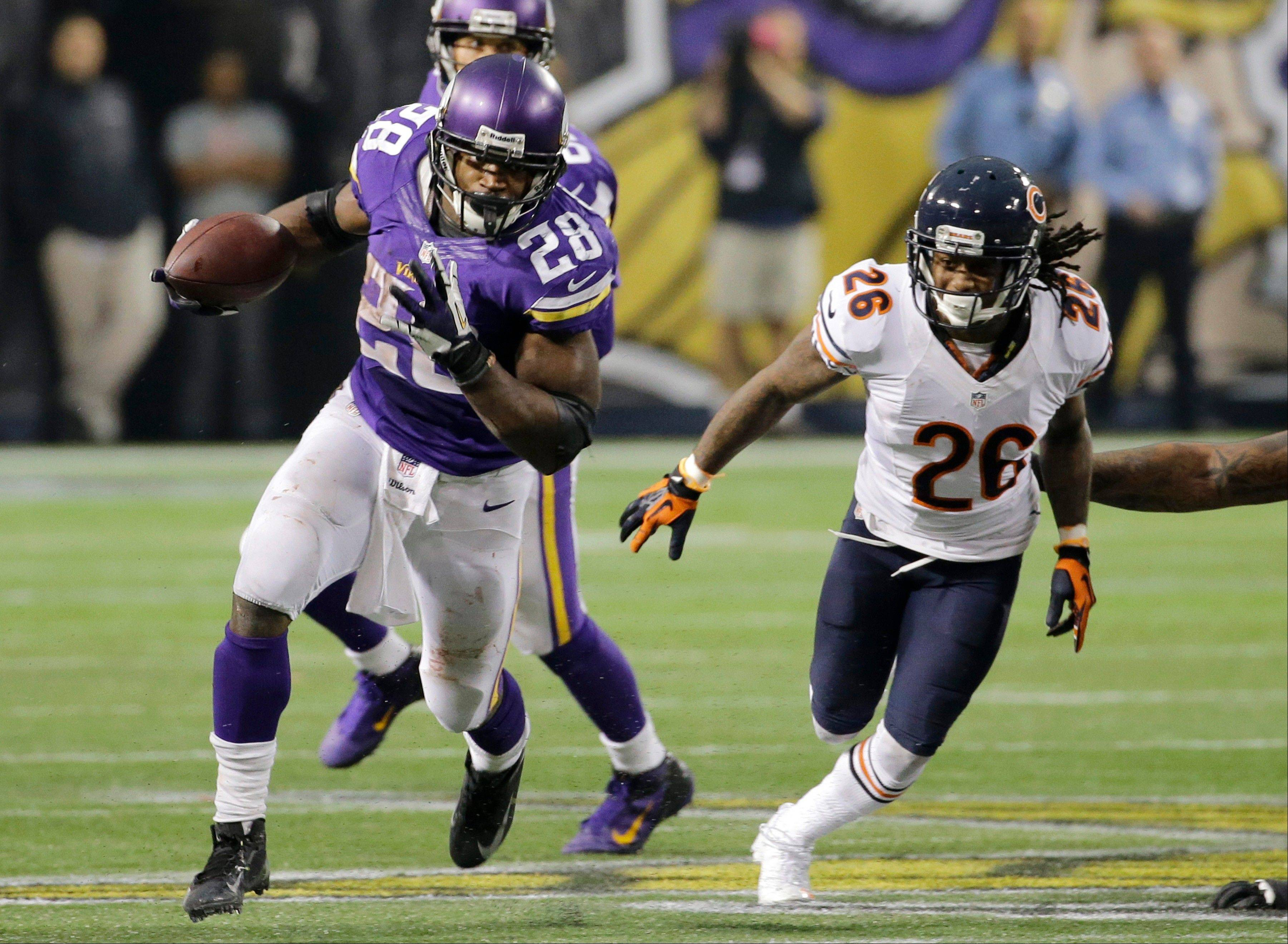 Minnesota Vikings running back Adrian Peterson (28) runs from Bears cornerback Tim Jennings during overtime of an NFL football game on Sunday, Dec. 1, 2013, in Minneapolis. The Vikings won 23-20.