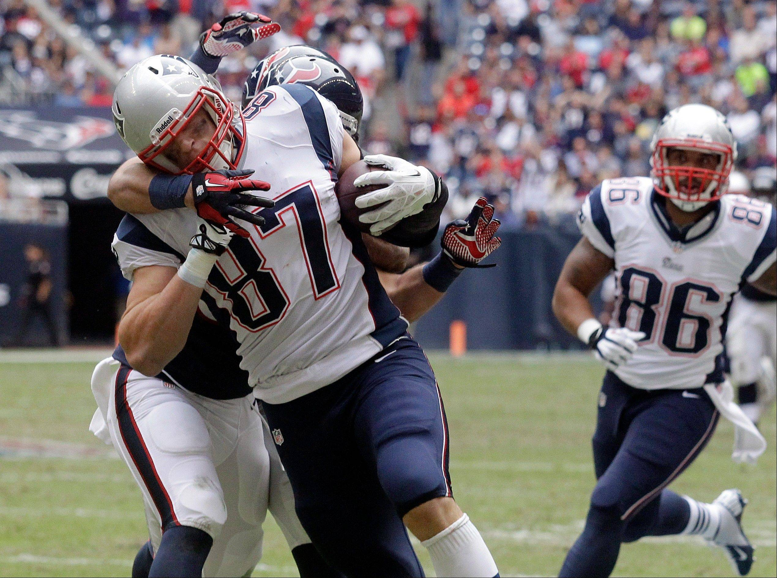 New England Patriots� Rob Gronkowski (87) is hit by Houston Texans� Shiloh Keo, left, after making a catch during the third quarter in Houston.