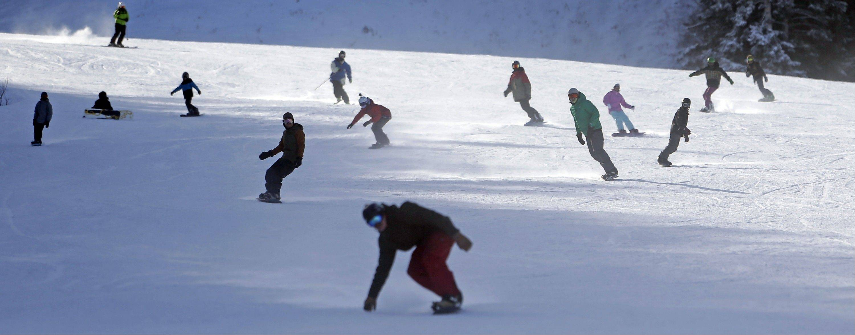 Skiers and snowboarders share a trail at Park City Mountain Resort in Utah.