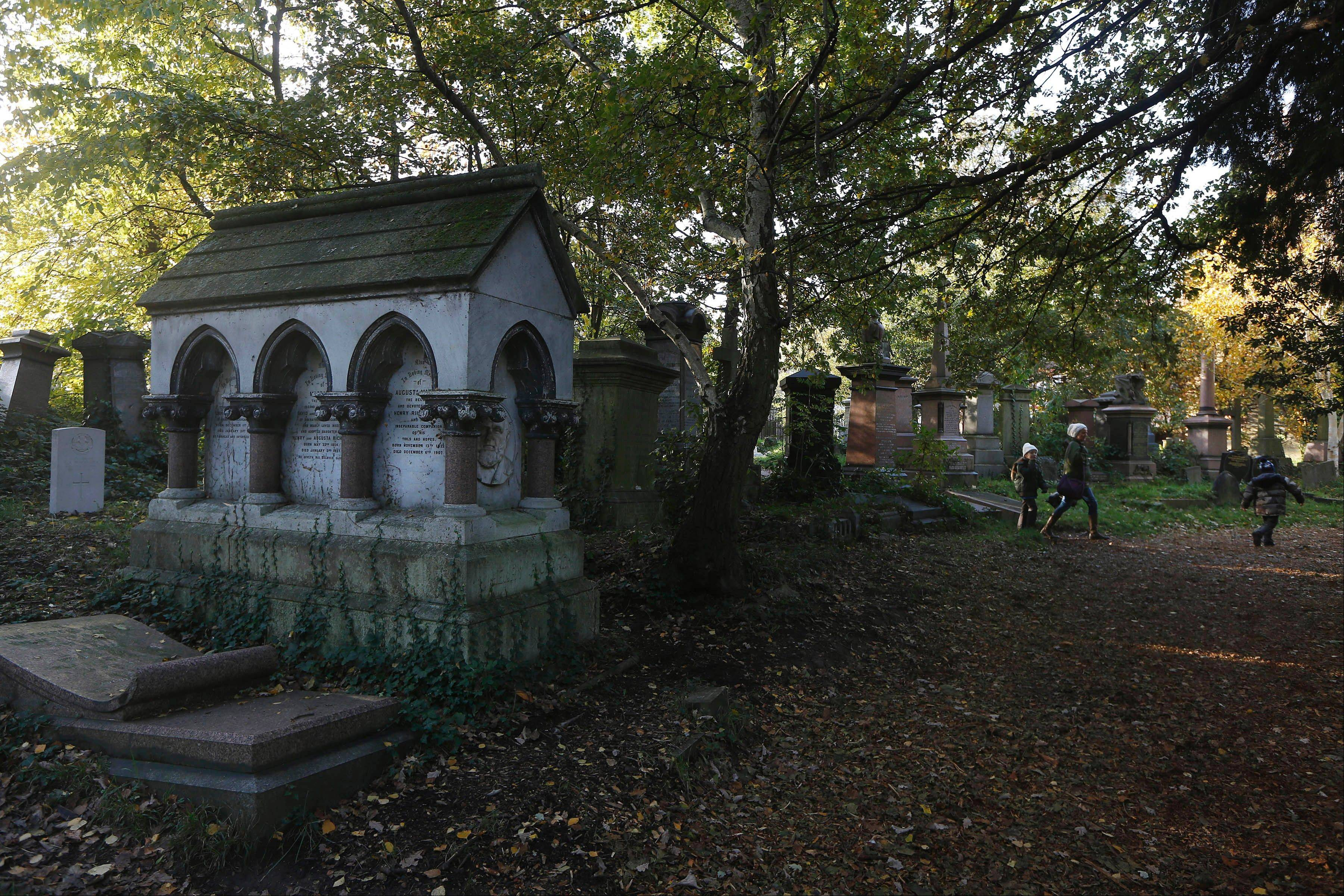 People walk through London's Abney Park Cemetery, which is a splendidly spooky, overgrown graveyard full of crumbling monuments and a ruined chapel, and it's free for visitors.