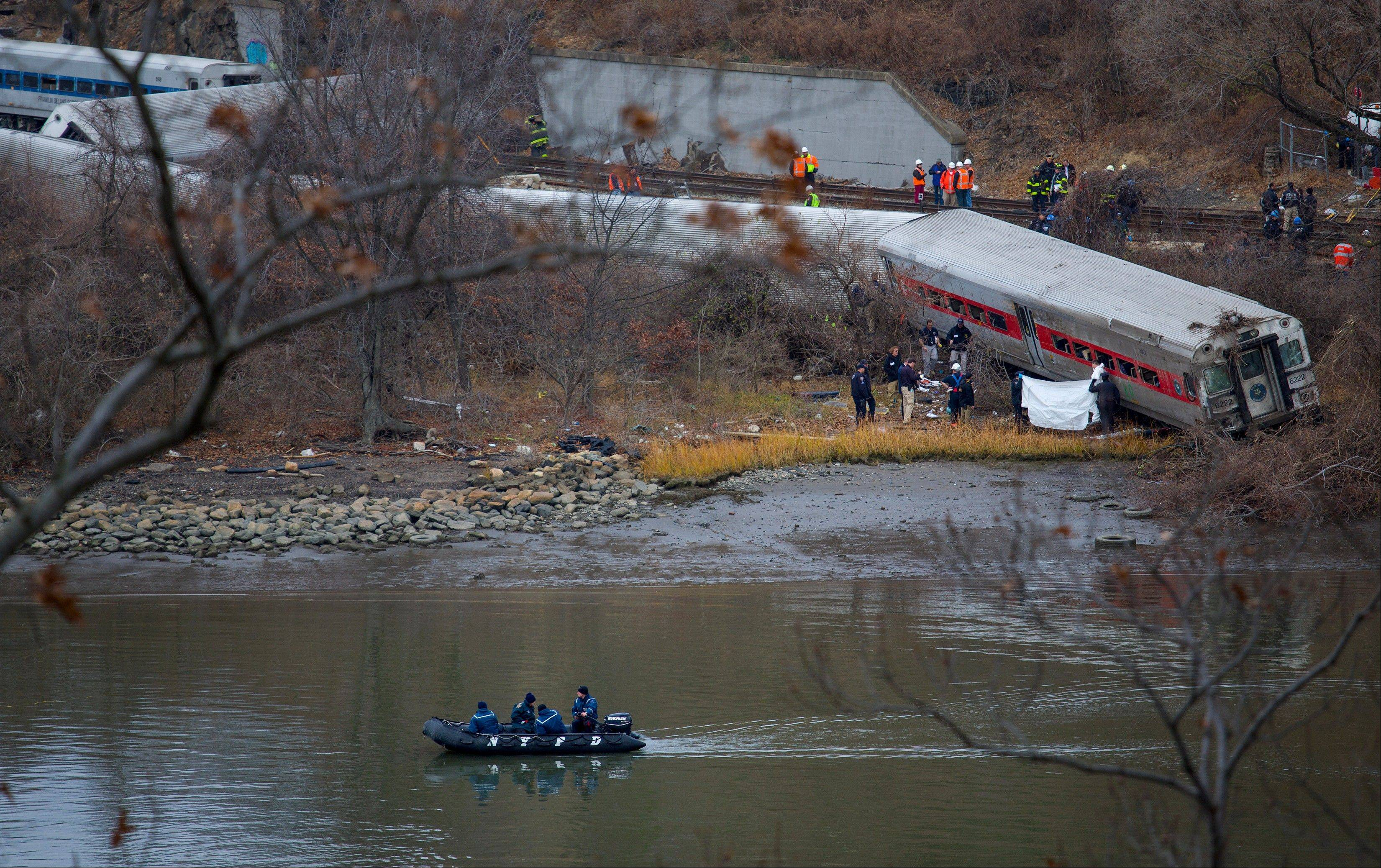 Viewed from Manhattan, first responders and others work near a victim next to a derailed Metro-North passenger train in the Bronx borough of New York.