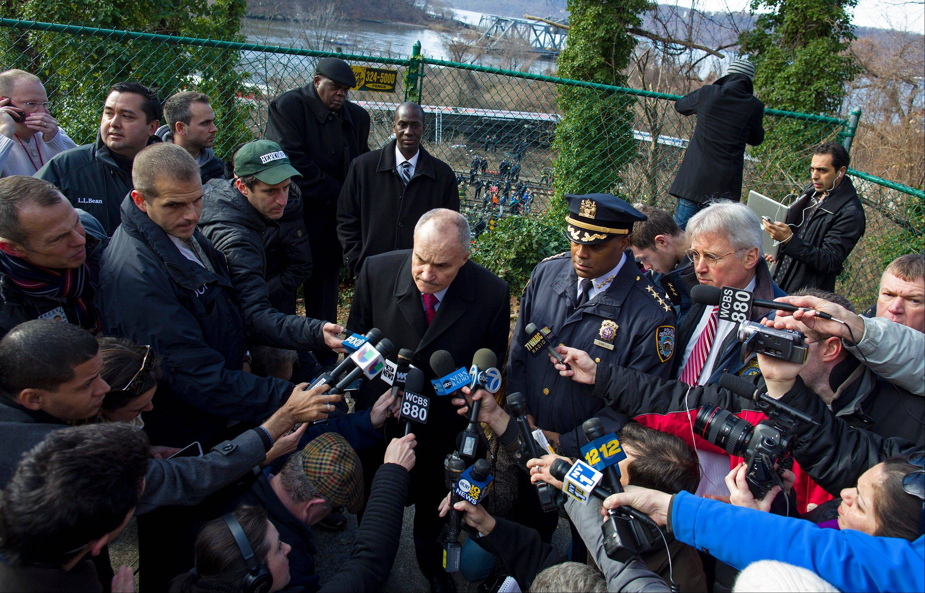 New York Police Commissioner Ray Kelly, center, takes questions from the media after the derailment of a Metro North passenger train, background, in the Bronx borough of New York, Sunday.