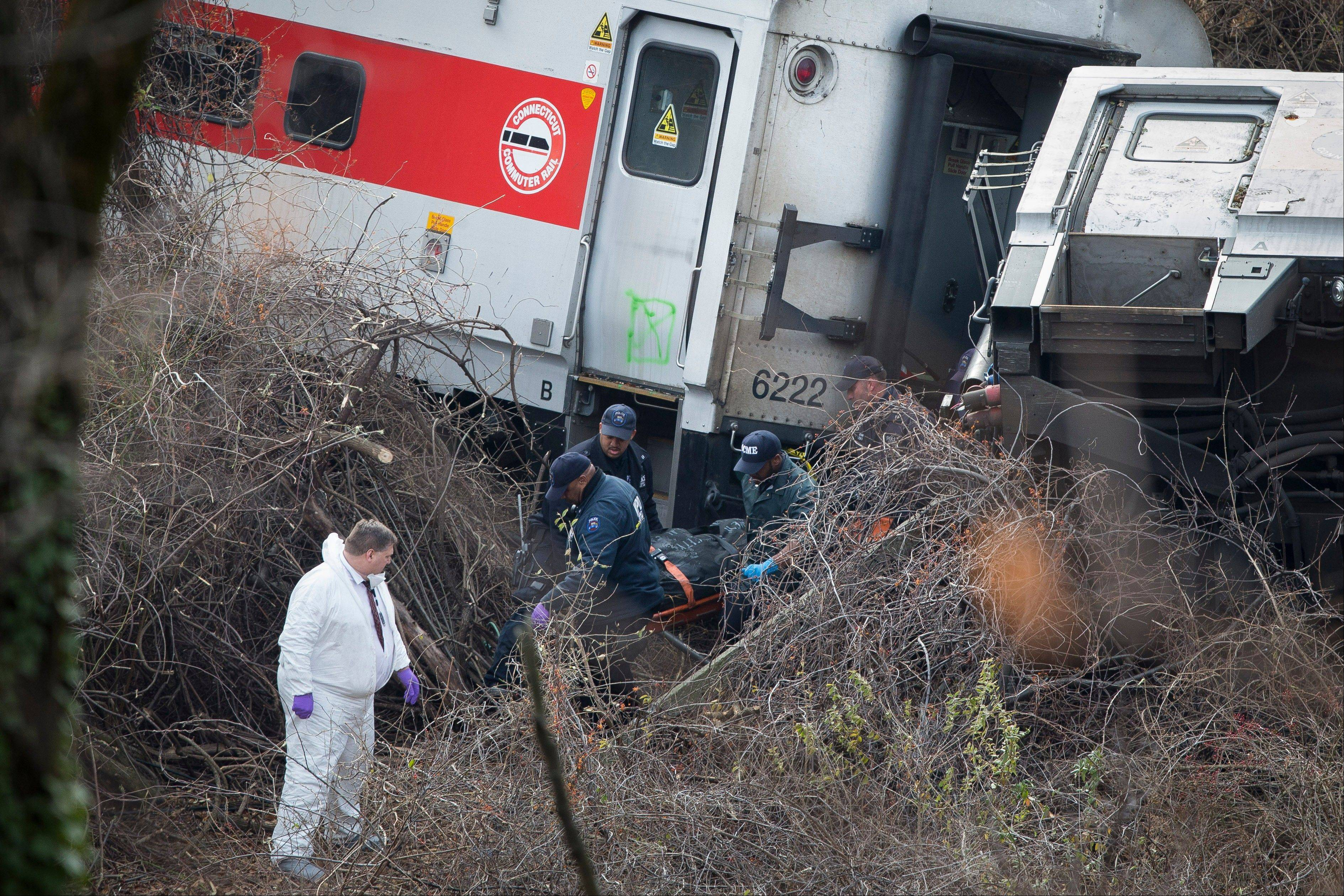 Emergency personnel remove a body from the scene of a Metro-North passenger train derailment in the Bronx borough of New York, Sunday.