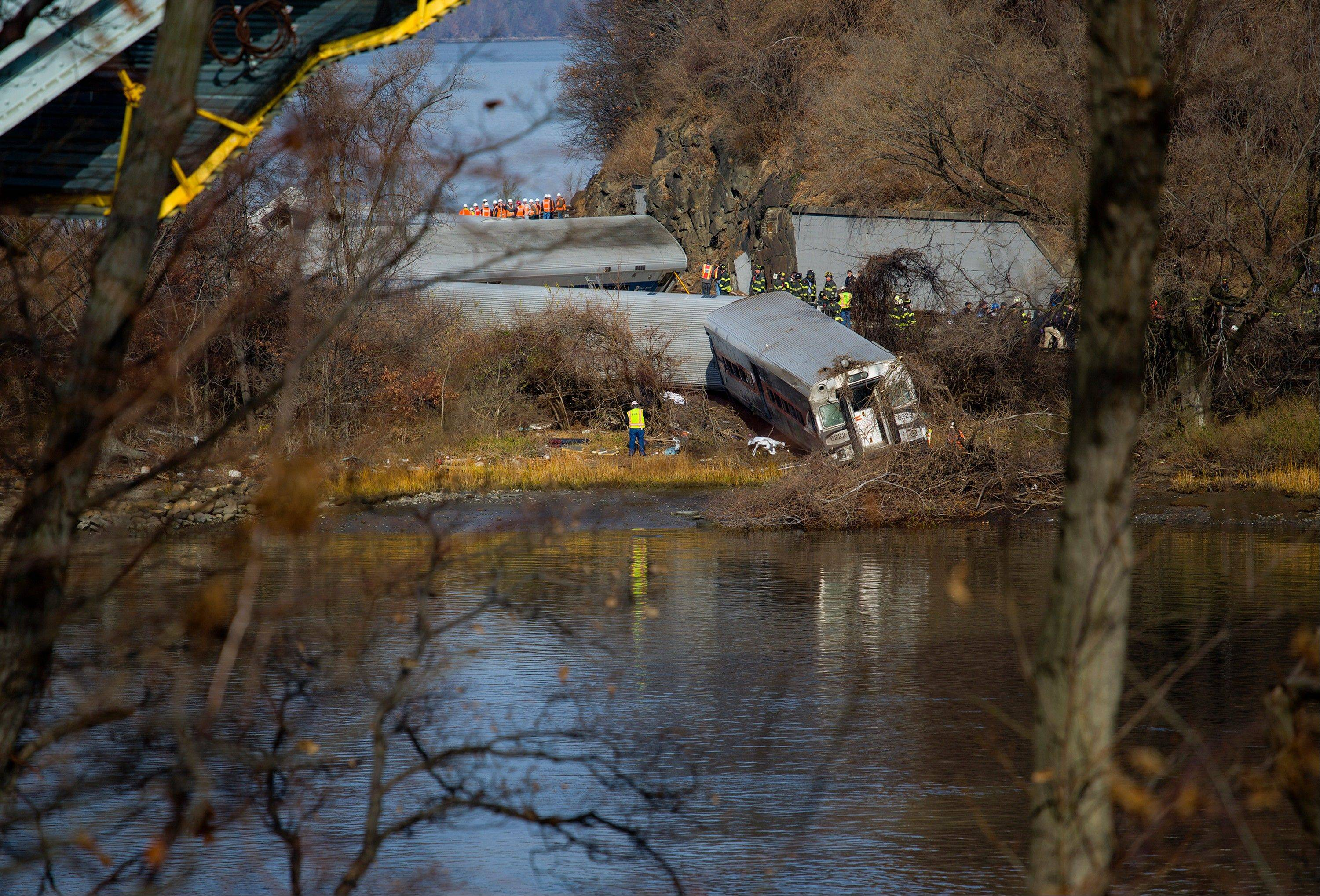 Viewed from Manhattan, Emergency rescue personnel work the scene of a Metro-North passenger train derailment in the Bronx borough of New York, Sunday.