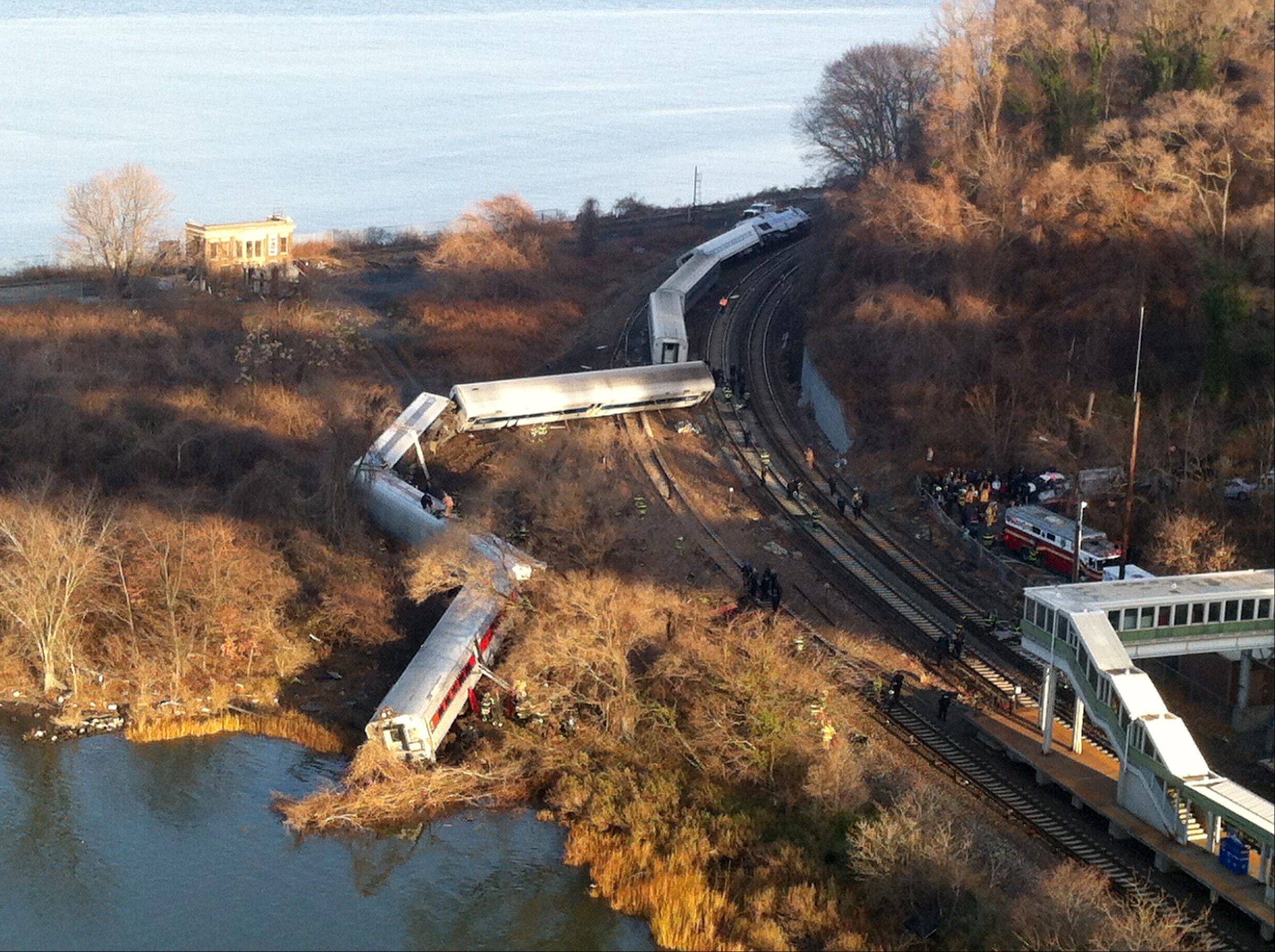 Cars from a Metro-North passenger train are scattered after the train derailed in the Bronx borough of New York, Sunday.