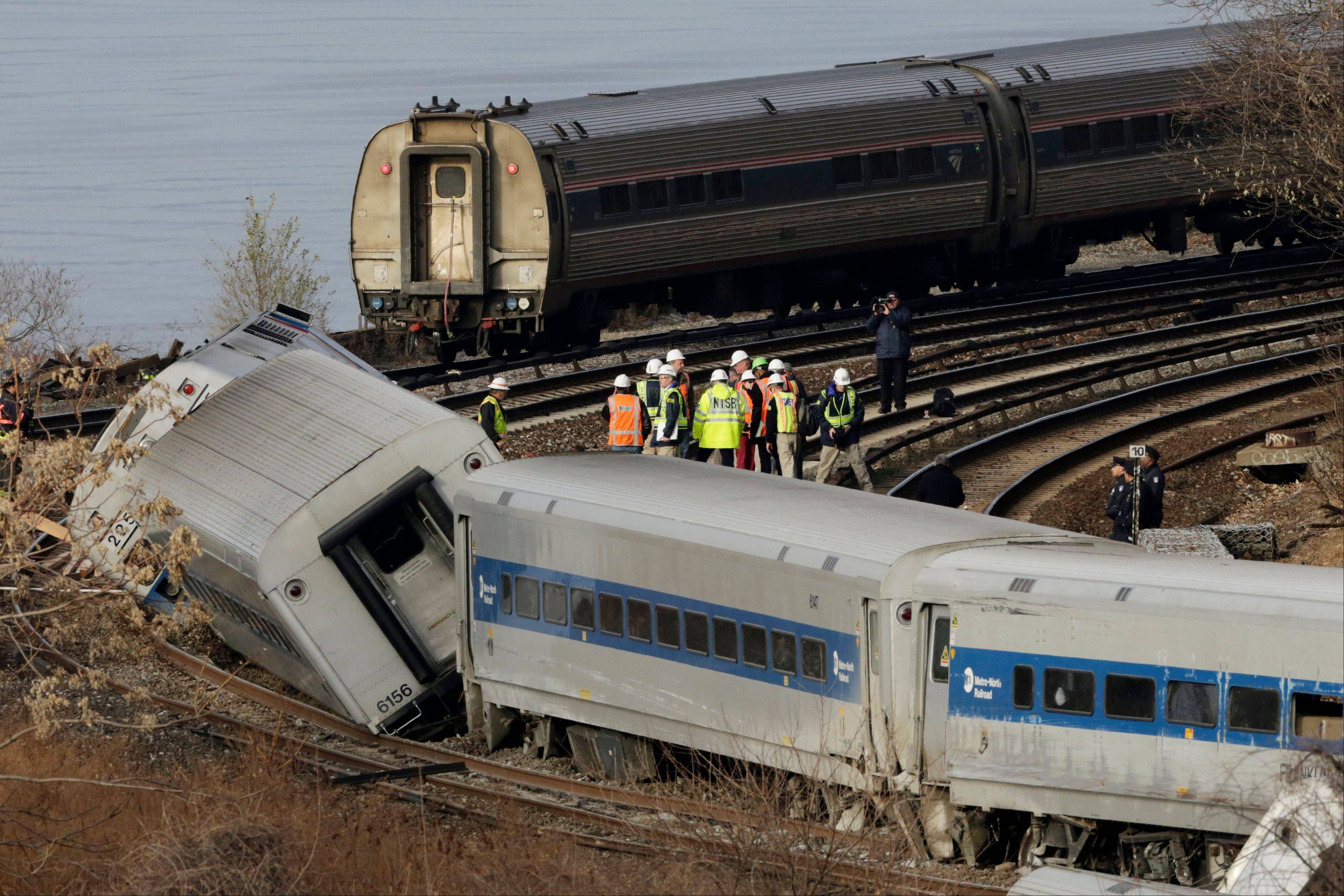 An Amtrak train, top, traveling on an unaffected track, passes a derailed Metro-North commuter train, Sunday.