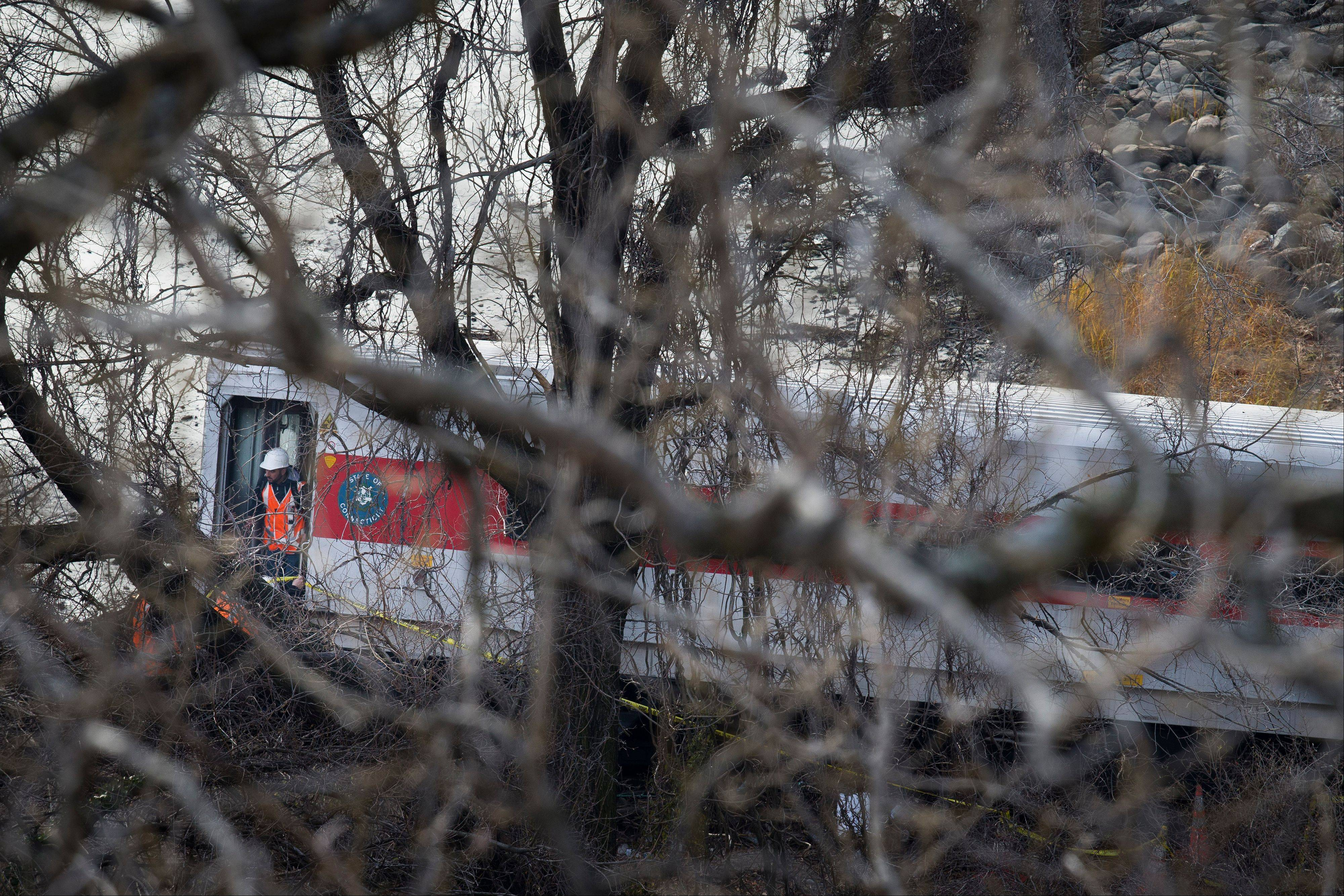 An emergency worker exits a derailed Metro-North passenger train a few feet from water in the Bronx borough of New York, Sunday.