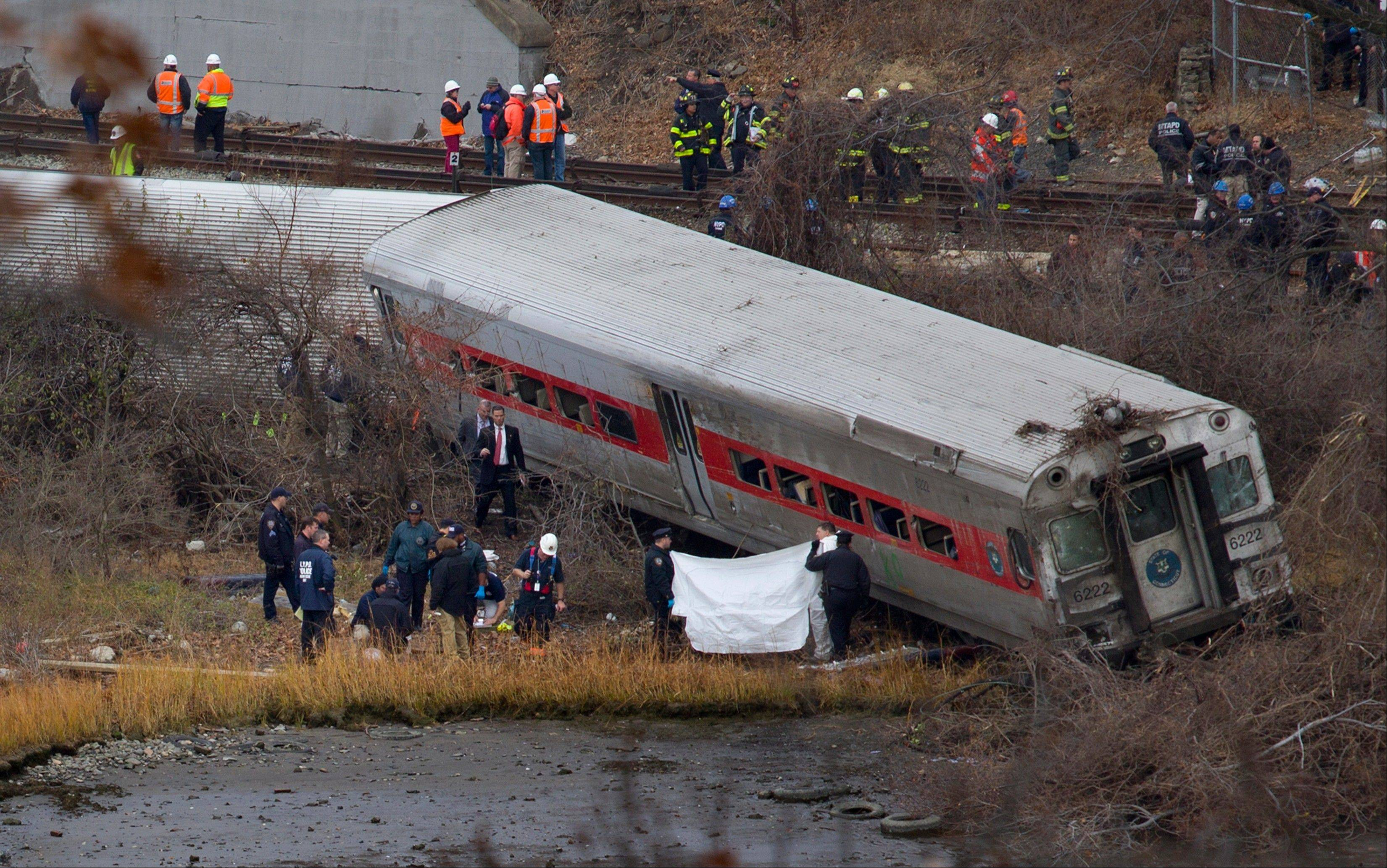 Viewed from Manhattan, first responders and others work at the scene of a derailed Metro North passenger train in the Bronx borough of New York.