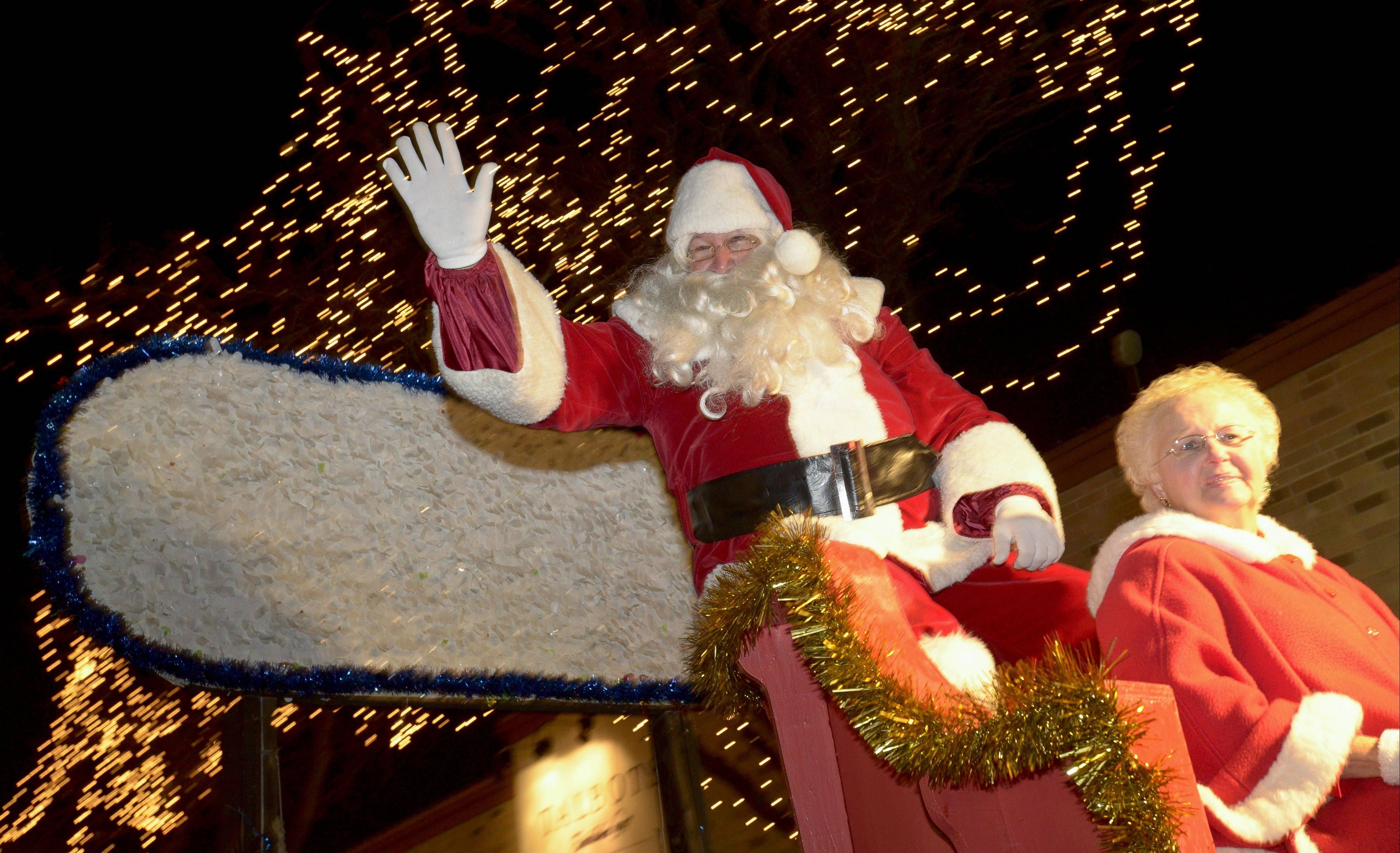 Santa travels down Main Street during the Little Friends Parade of Lights Sunday in downtown Naperville.