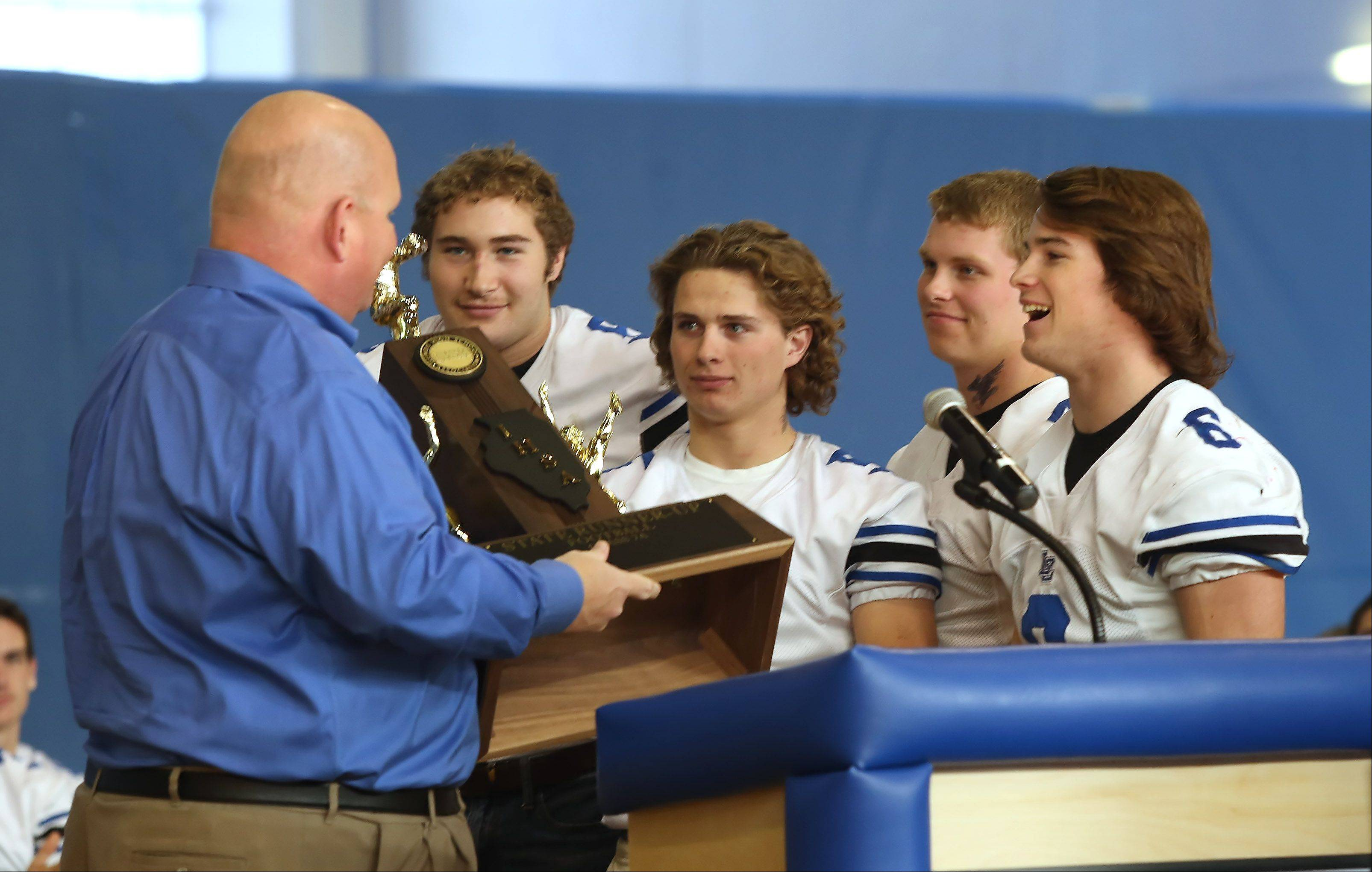 Team captains Sean Lynch, right, Noah Allgood, Sam Walstrom and Colton Moskal present their trophy to Principal Kent Nightlinger during a rally Sunday for the Lake Zurich High School football team.