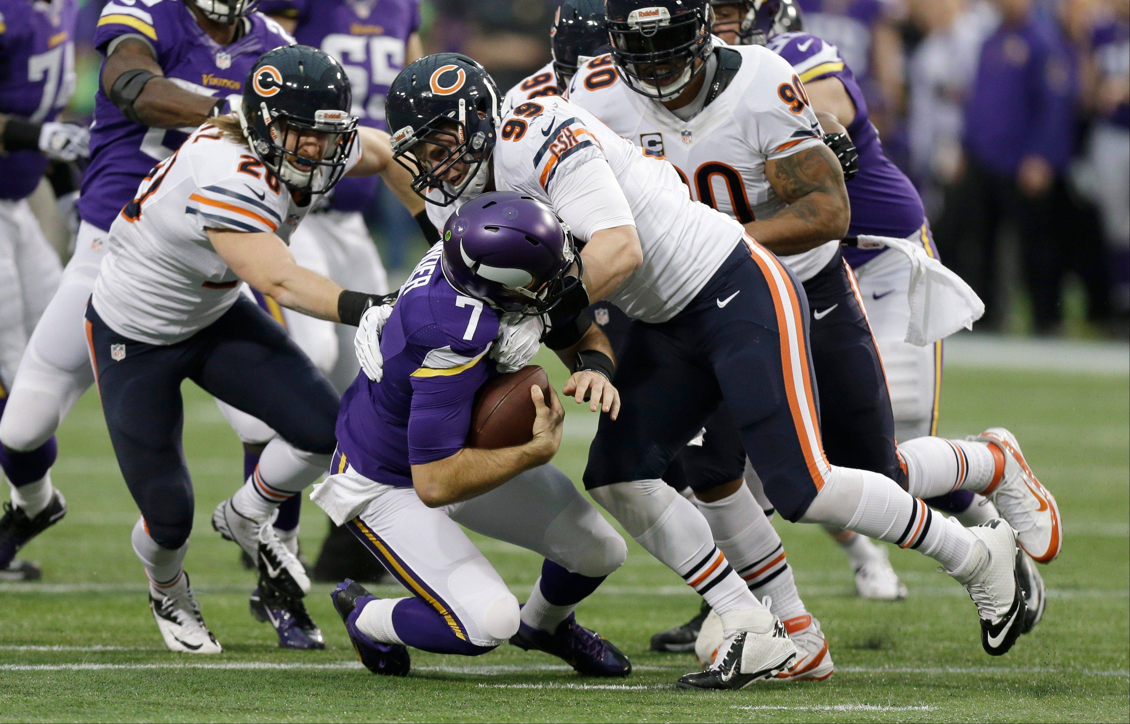 Minnesota Vikings quarterback Christian Ponder (7) is sacked by Chicago Bears defensive end Shea McClellin, right, and strong safety Craig Steltz, left, during the first half.