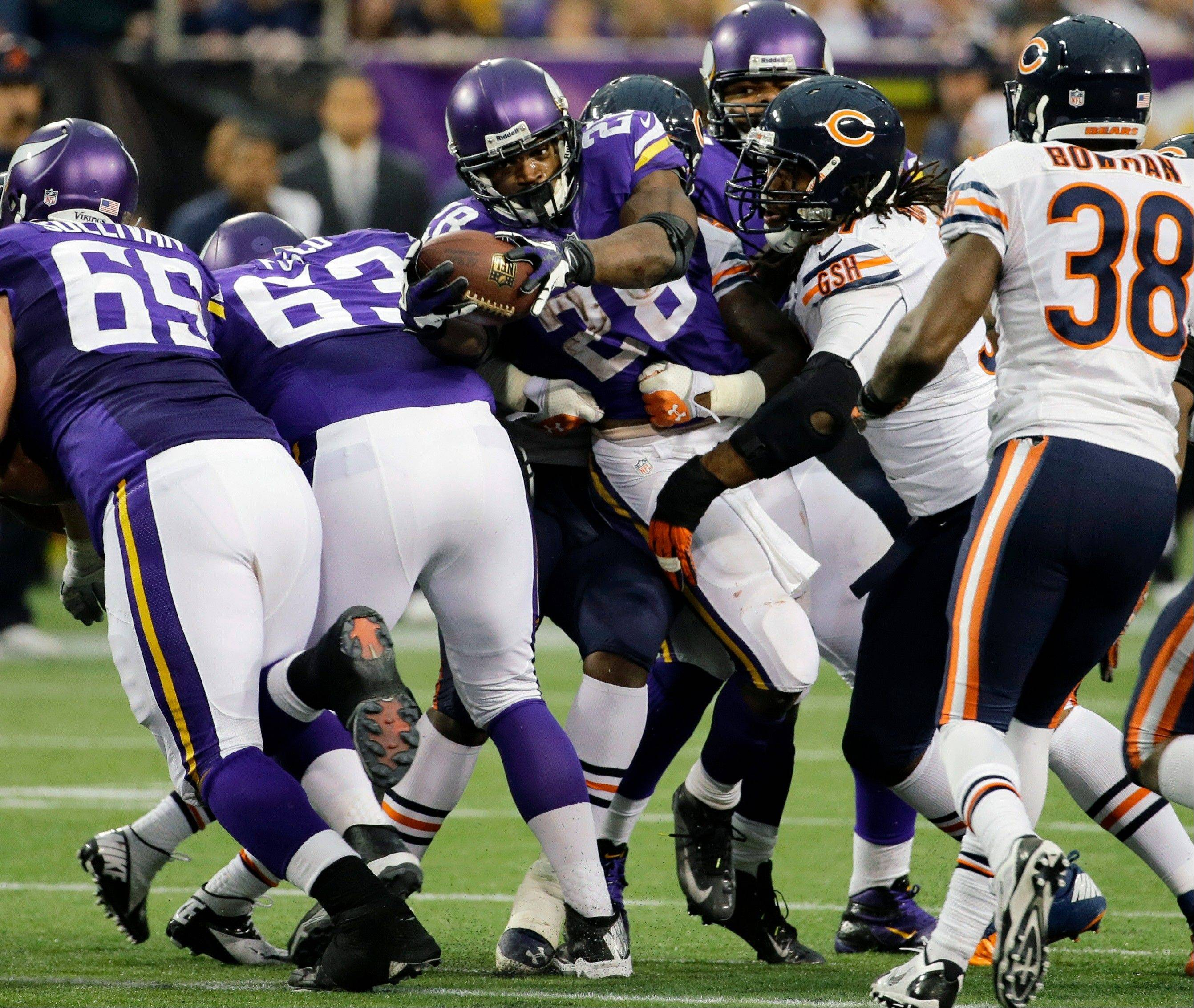 Minnesota Vikings running back Adrian Peterson, center, fights for extra yardage during the second half.