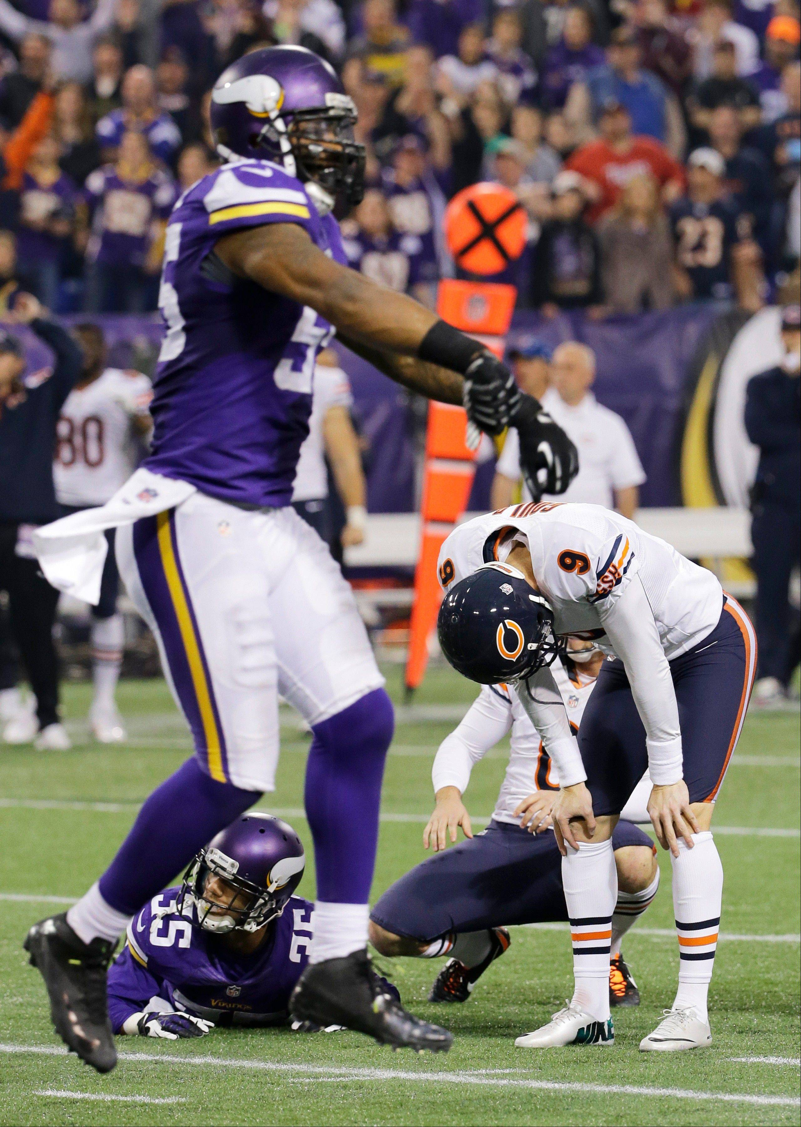 Chicago Bears kicker Robbie Gould (9) reacts in front of Minnesota Vikings defenders Marcus Sherels (35) and Marvin Mitchell after missing a field goal during overtime of an NFL football game. The Vikings won 23-20.