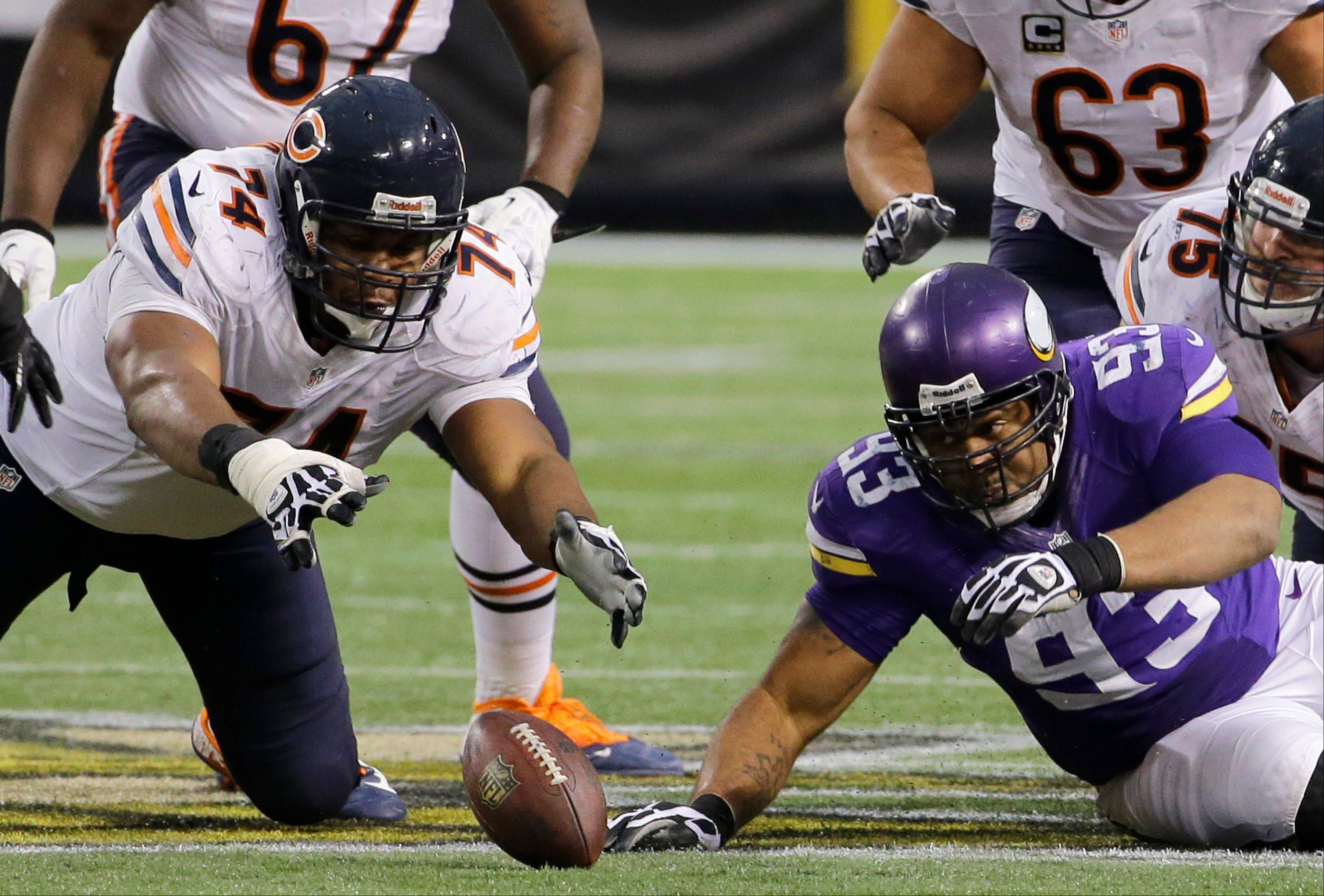 Chicago Bears tackle Jermon Bushrod, left, and Minnesota Vikings defensive tackle Kevin Williams, right, eye a fumble during the fourth quarter. The Vikings won 23-20 in overtime.