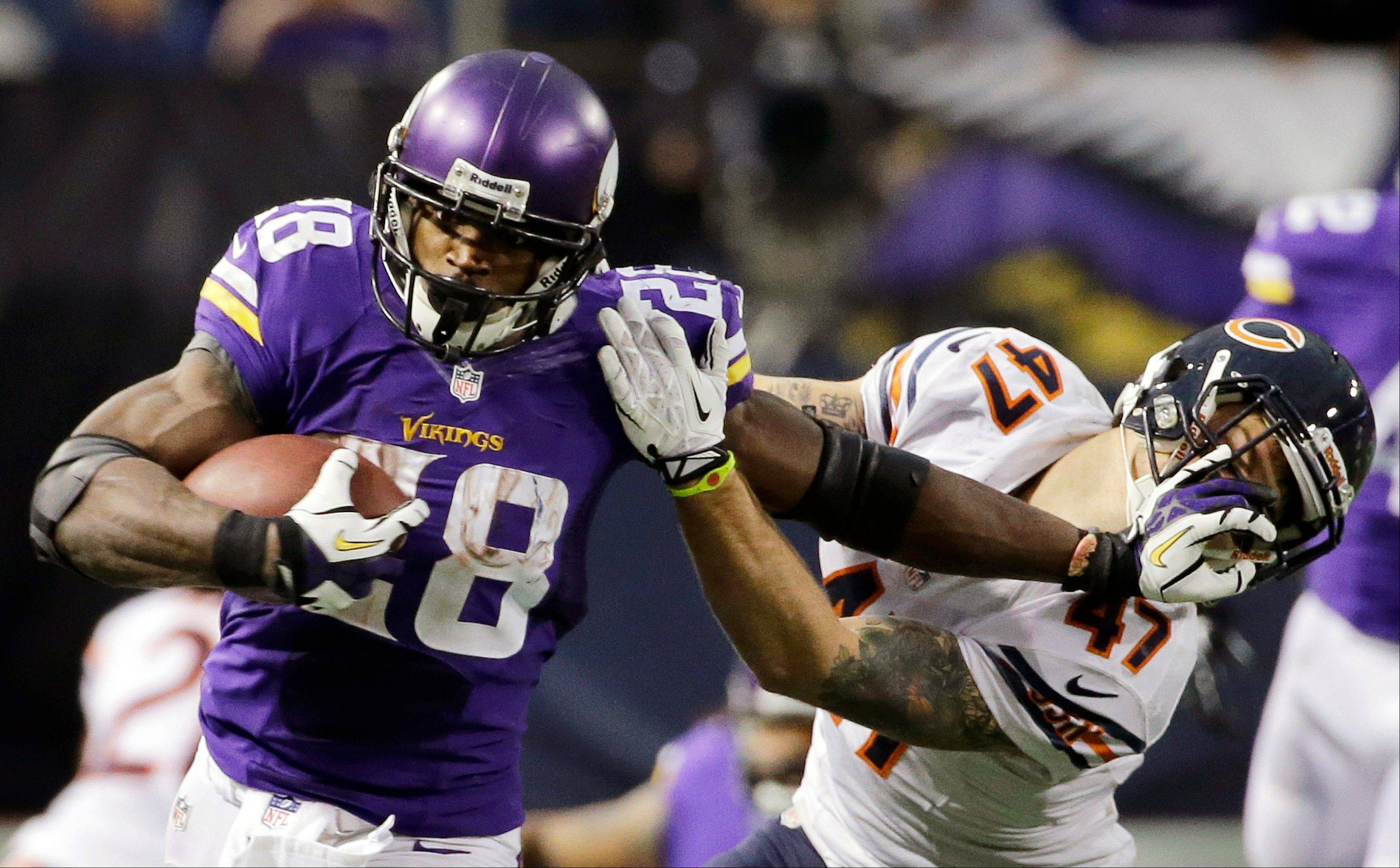Minnesota Vikings running back Adrian Peterson, left, tries to break a tackle from Chicago Bears free safety Chris Conte during the fourth quarter.