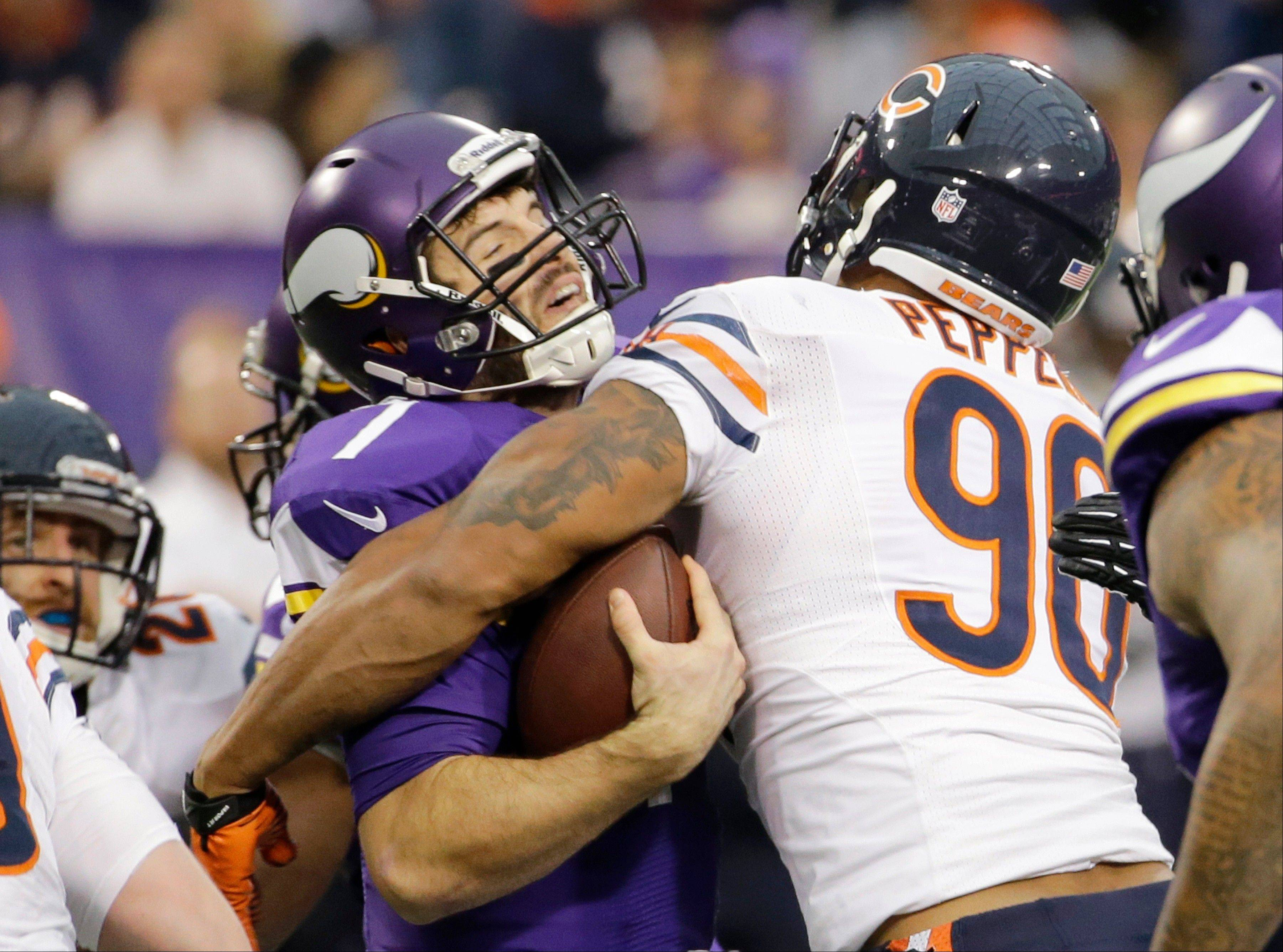 Minnesota Vikings quarterback Christian Ponder, left, is sacked by Chicago Bears defensive end Julius Peppers during the first half.