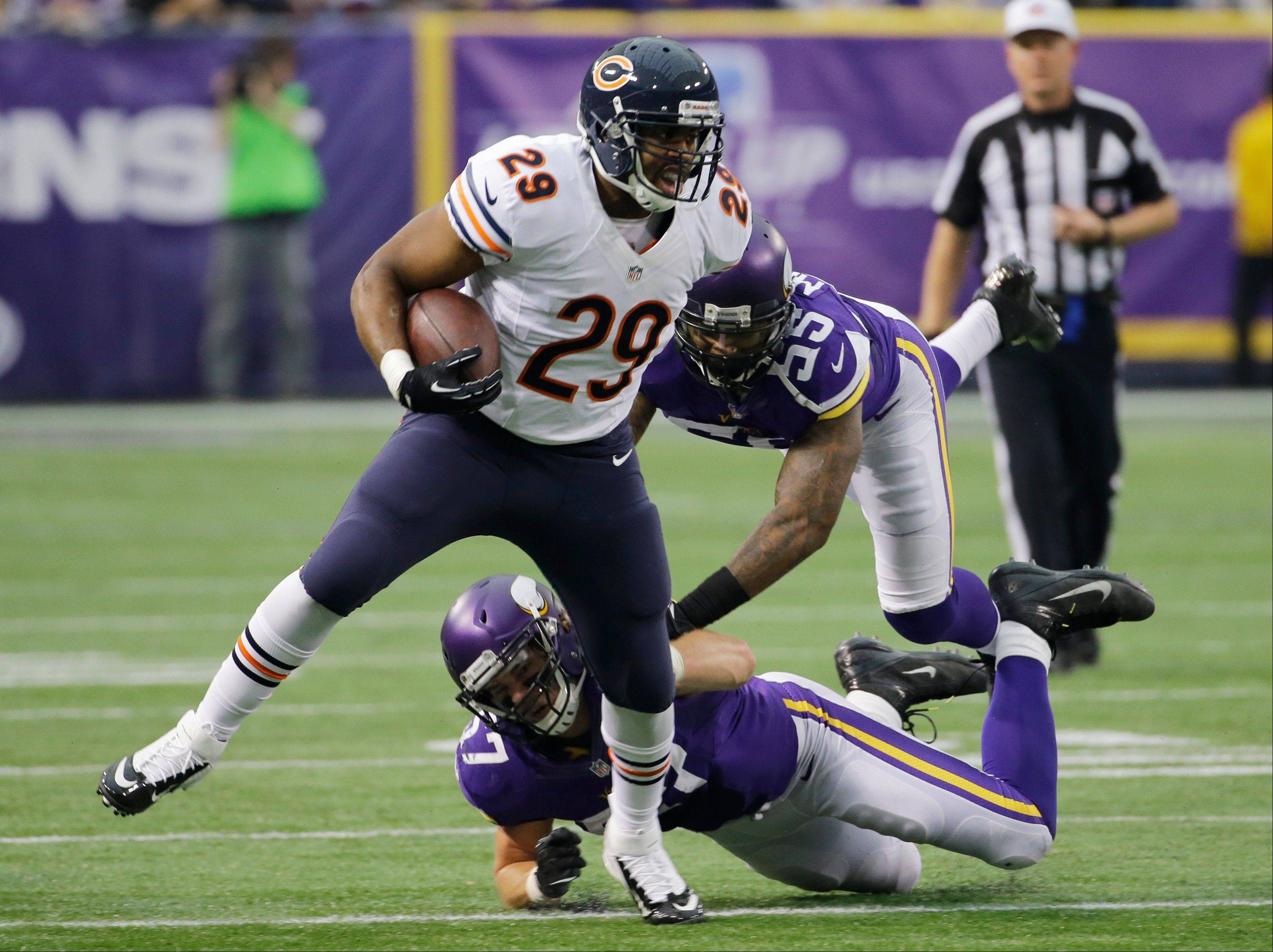 Chicago Bears running back Michael Bush (29) runs from Minnesota Vikings defenders Audie Cole and Marvin Mitchell (55) during the first half.