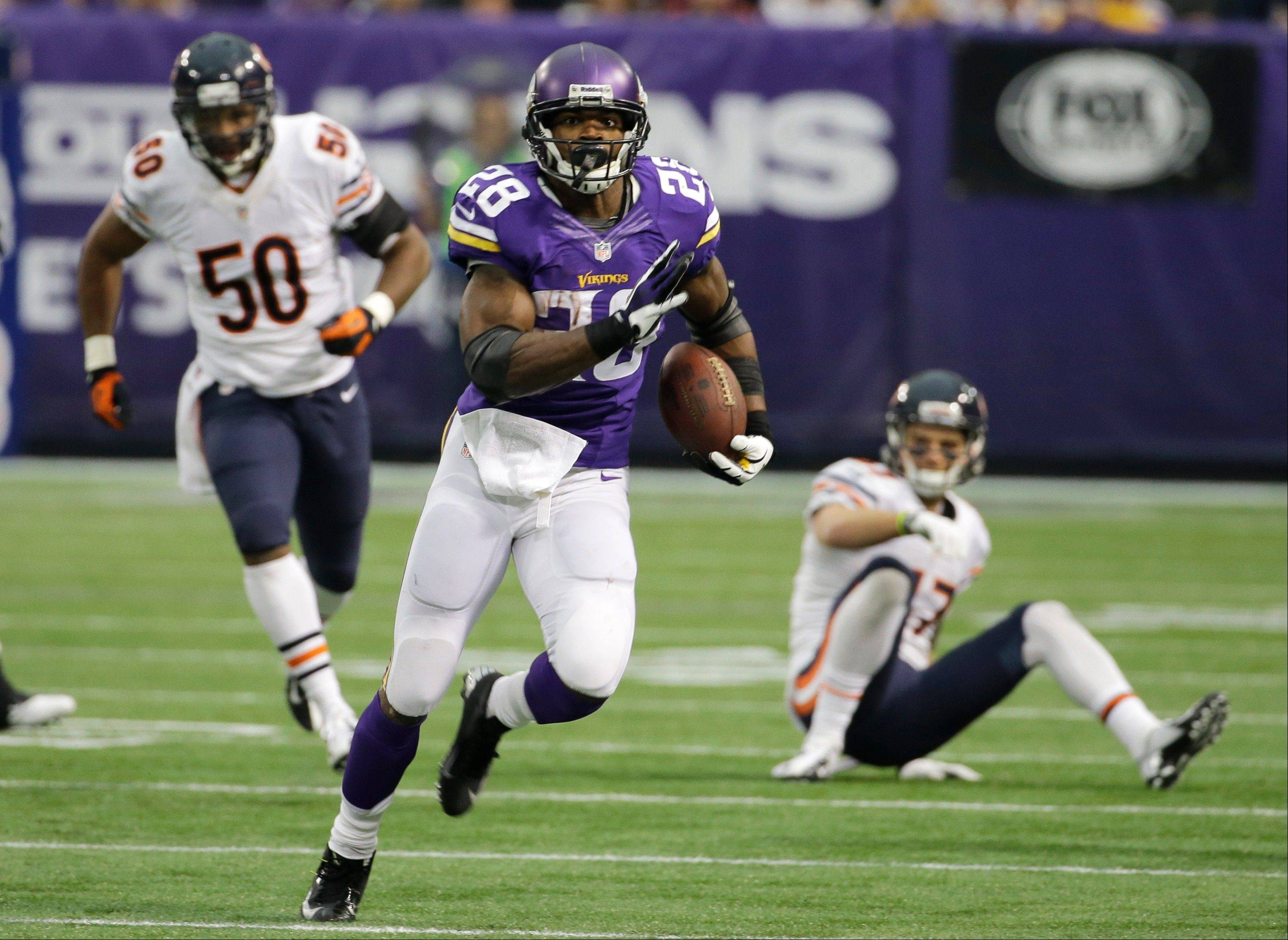 Minnesota Vikings running back Adrian Peterson, center, runs from Chicago Bears defenders James Anderson, left, and Chris Conte, right, during the first half.