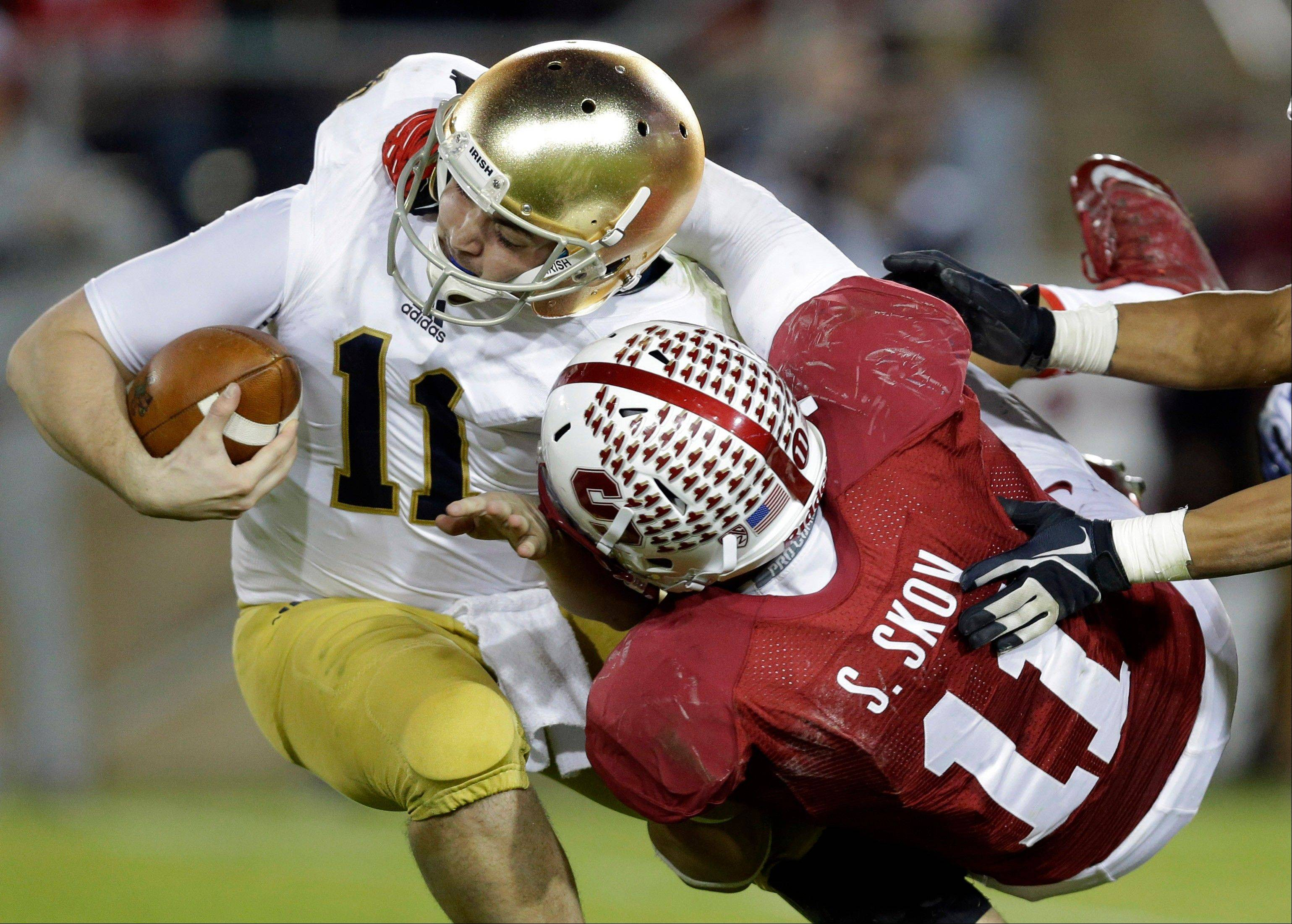 Notre Dame quarterback Tommy Rees, left, is sacked by Stanford linebacker Shayne Skov during the second half of an NCAA college football game on Saturday, Nov. 30, 2013, in Stanford, Calif. Stanford won 27-20.