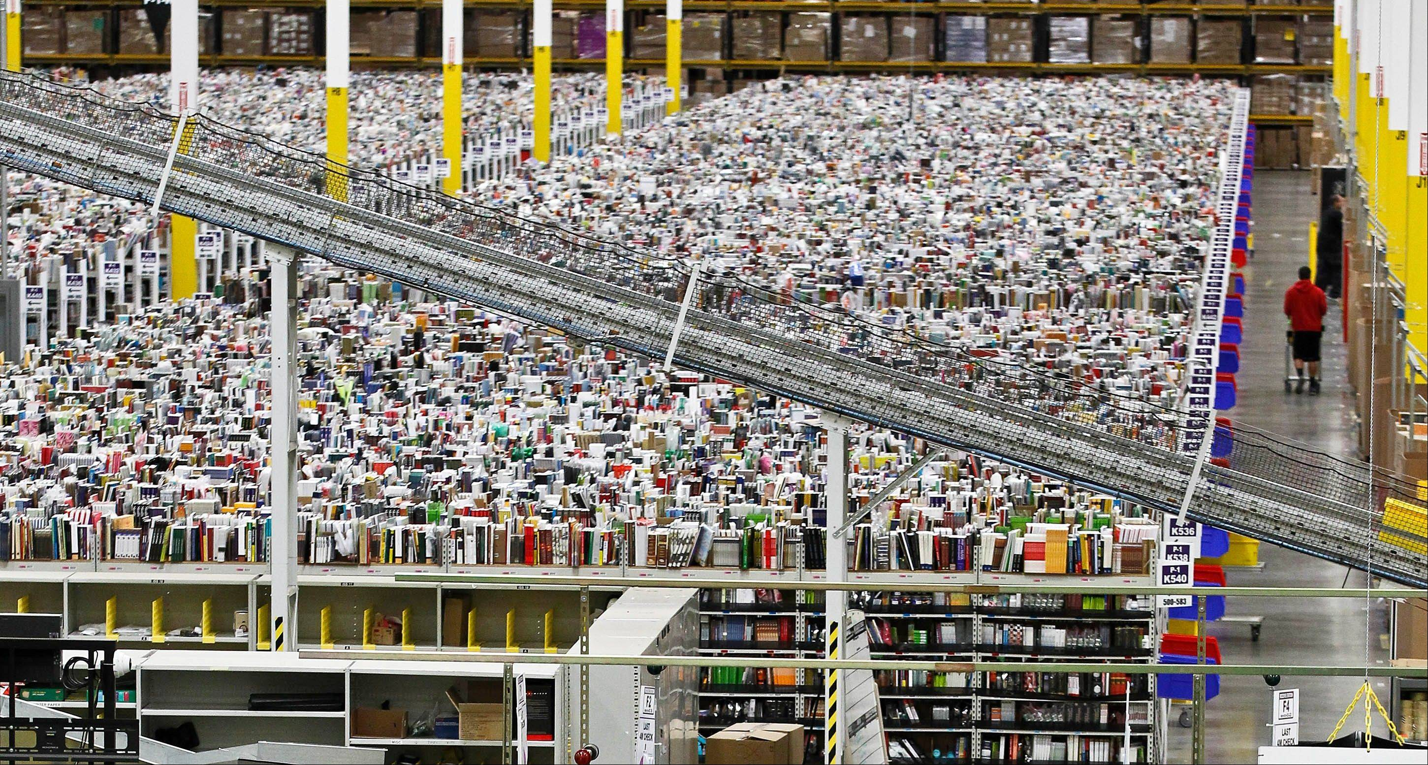 An employee walks a wide isle at Amazon.com�s 1.2 million square foot fulfillment center, in Phoenix. Millions of shoppers are expected to click on items this holiday season, but few states will see any of the sales tax those purchases would normally generate.