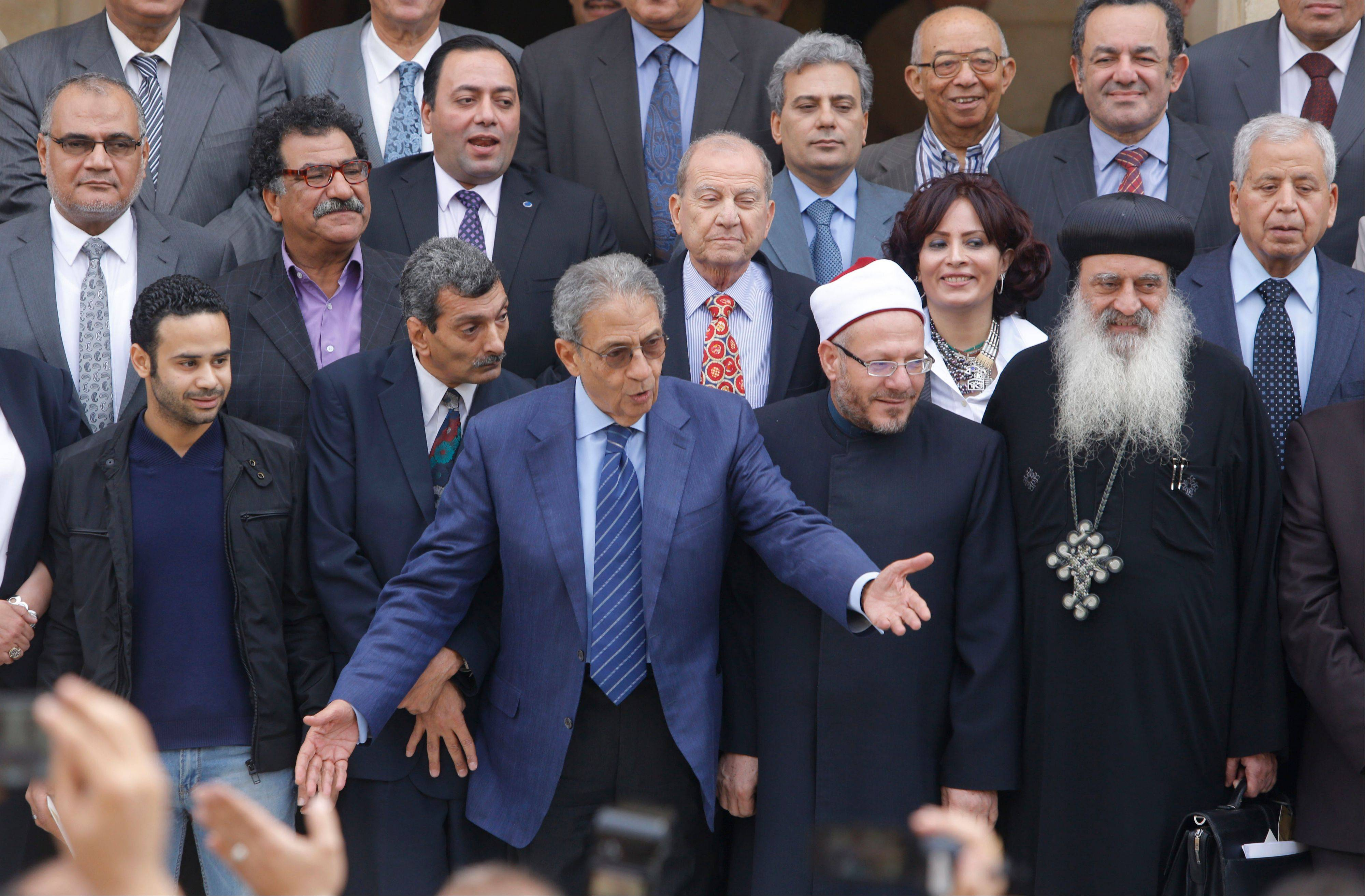 Amr Moussa, center, chairman of Egypt�s 50-member panel tasked with amending Egypt�s Islamist-drafted constitution, arranges the members for a group picture after finishing the final draft of a series of constitutional amendments at the Shoura Council in Cairo on Monday.