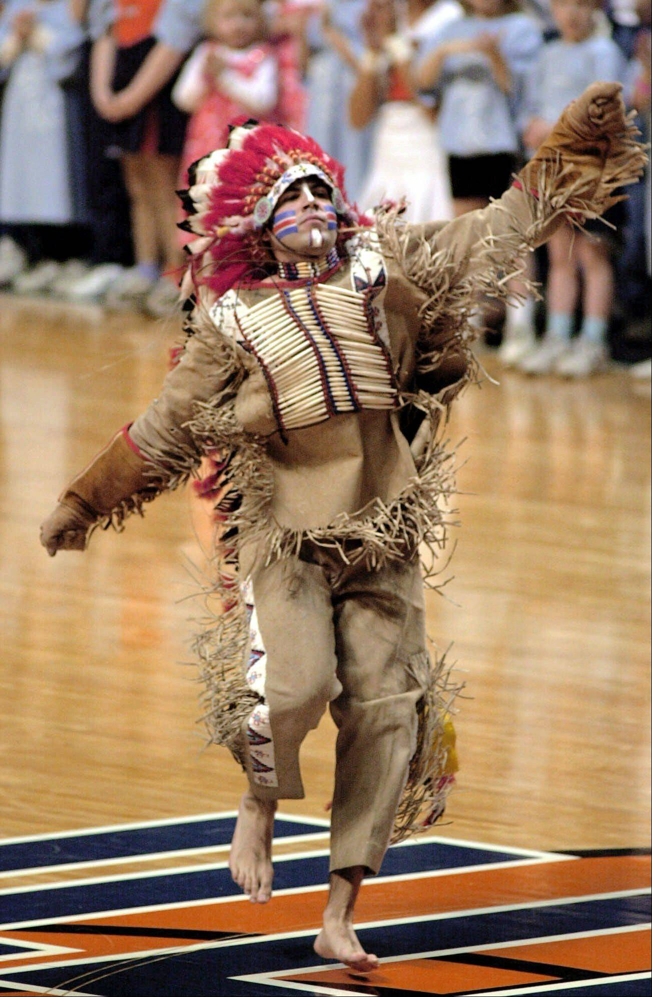 In this photo from 2000, the University of Illinois' mascot Chief Illiniwek dances for the crowd at a women's basketball game, in Champaign. The university retired Chief Illiniwek as a mascot in 2007. But the school kept the name of the Fighting Illini.