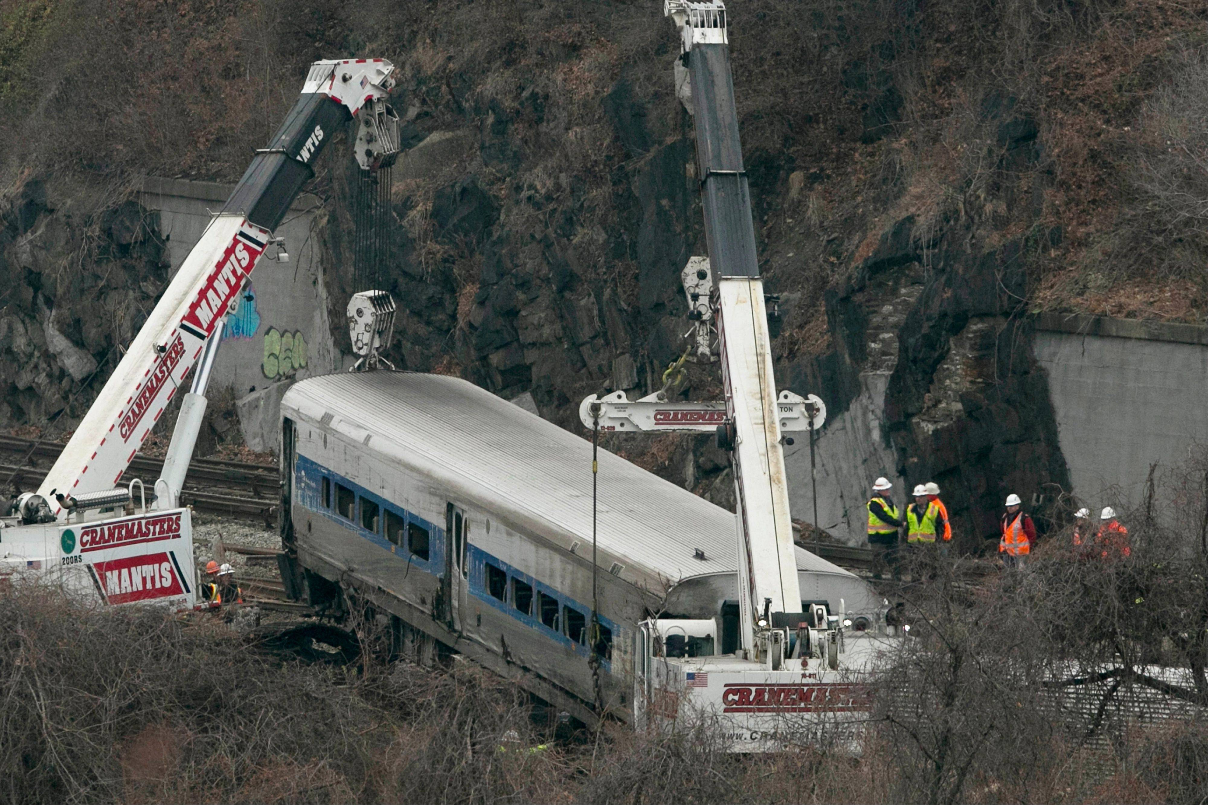 Cranes lift a derailed Metro North train car Monday in the Bronx borough of New York, when federal authorities began righting the cars as they investigated what caused a the commuter train rounding a riverside curve to derail.