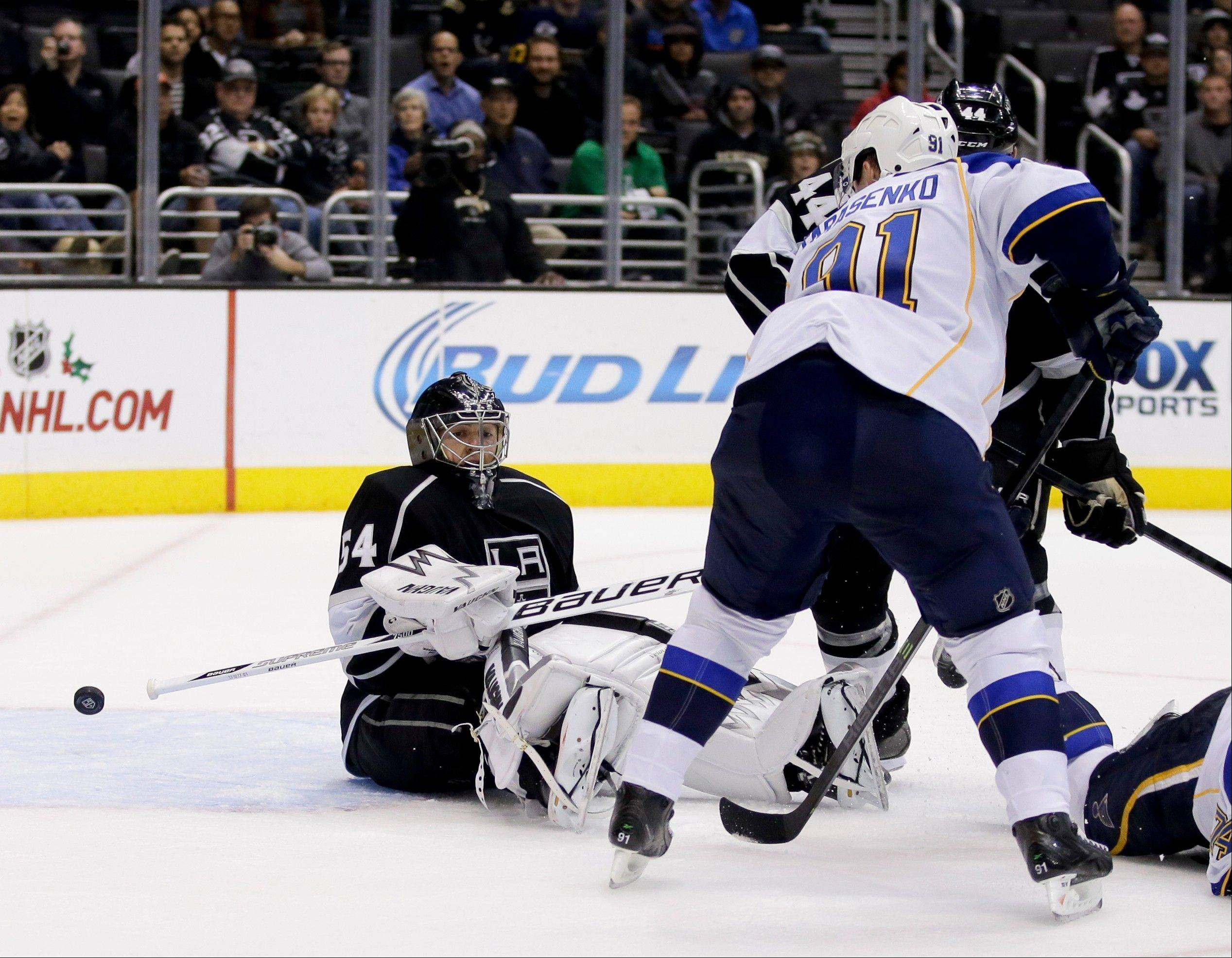 St. Louis Blues right wing Vladimir Tarasenko, left, scores past Los Angeles Kings goalie Ben Scrivens during the third period of an NHL hockey game Monday in Los Angeles.