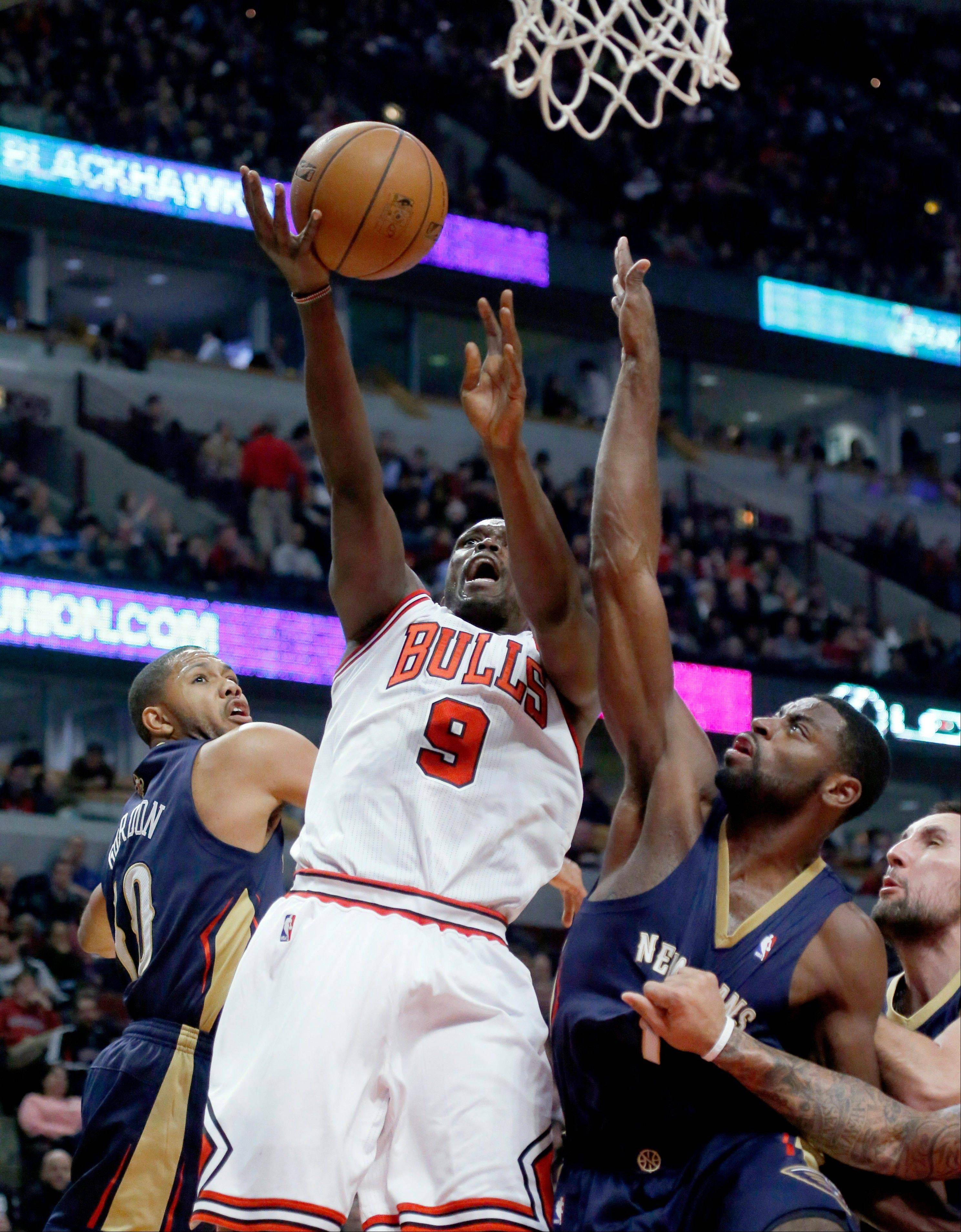 Bulls forward Luol Deng shoots over Pelicans guards Eric Gordon, left, and Tyreke Evans. Deng finished with 37 points.