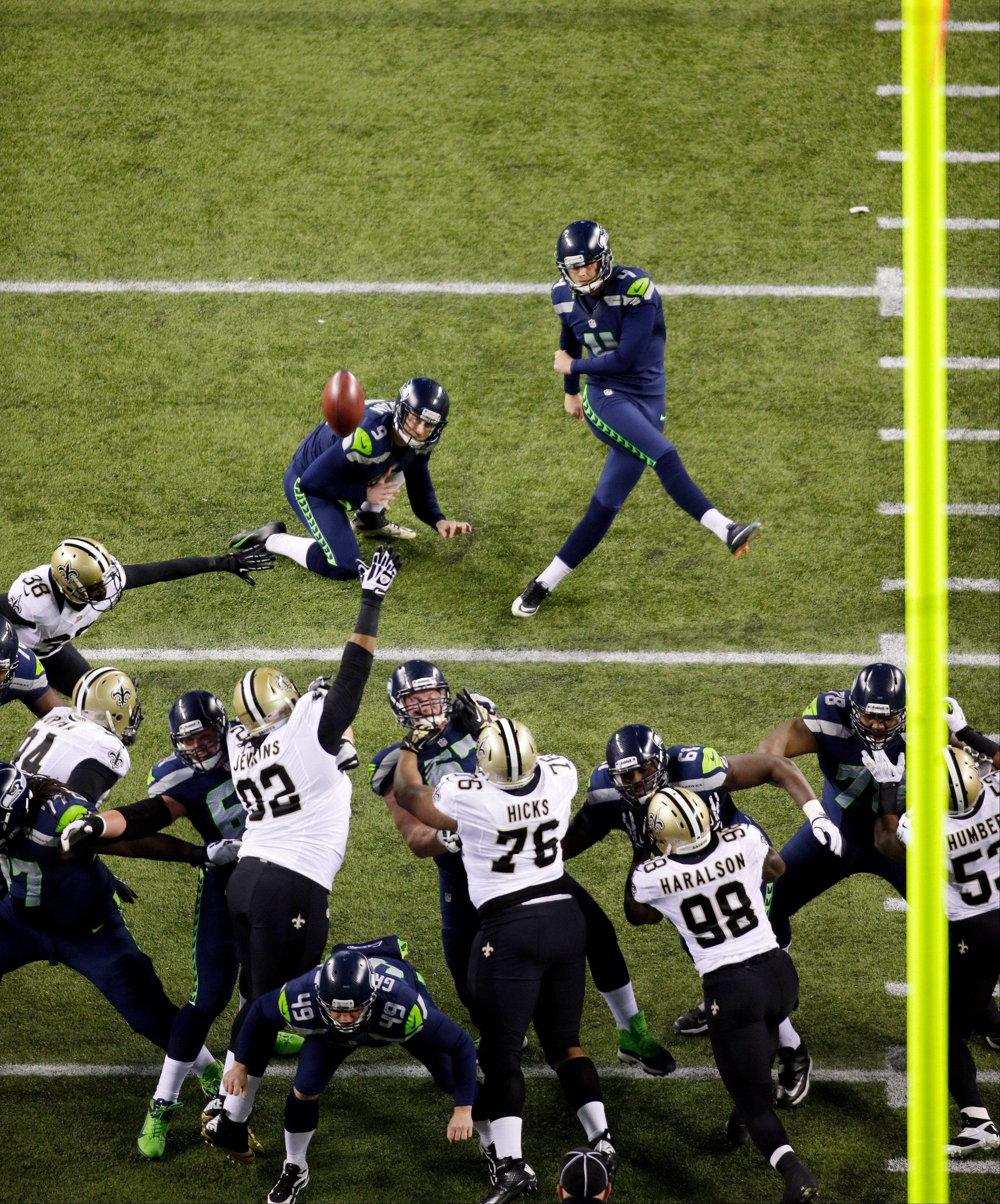 Seattle Seahawks kicker Steven Hauschka, upper right, kicks a field goal as Seahawks' Jon Ryan holds in the first half of an NFL football game Monday against the New Orleans Saints in Seattle.